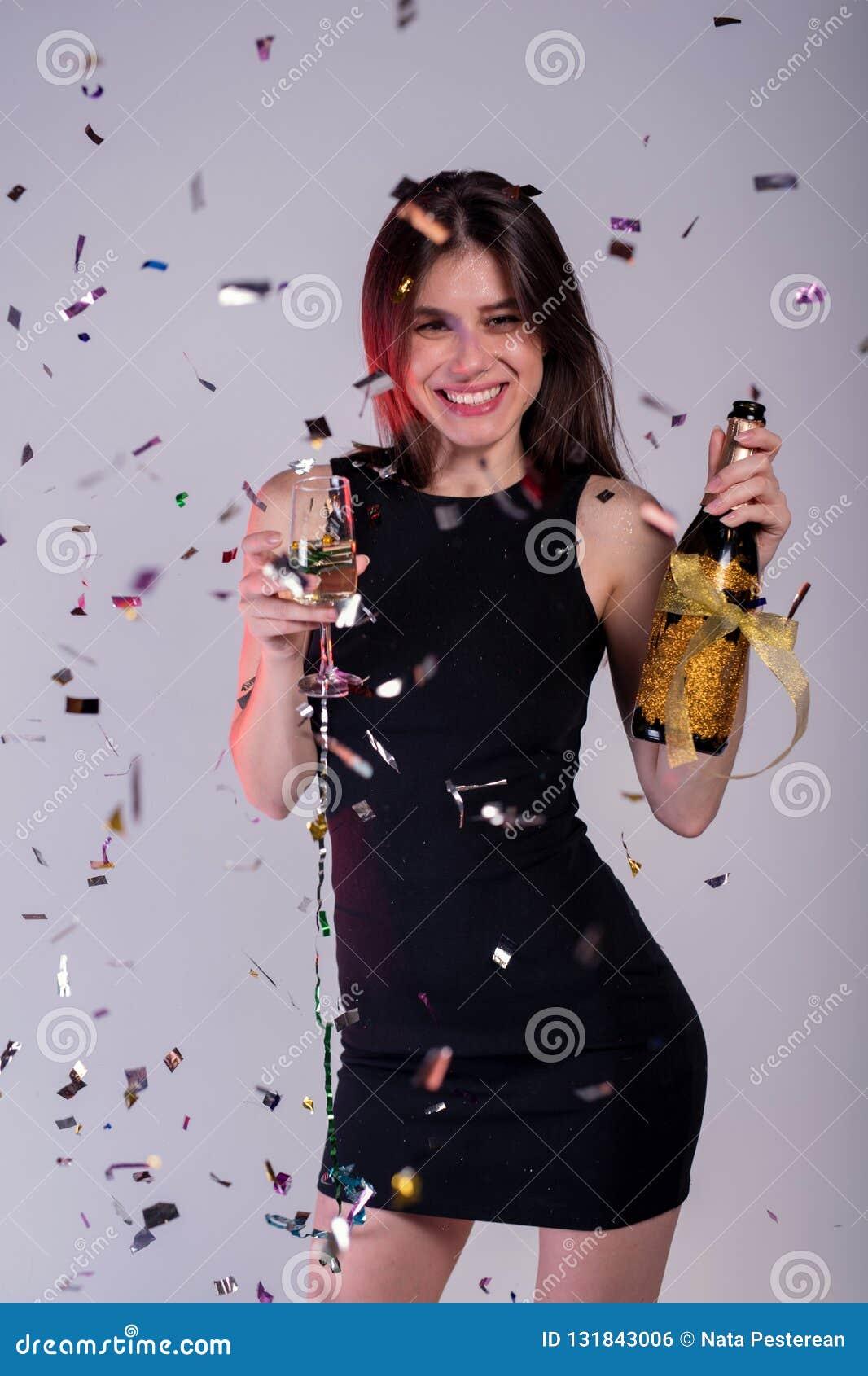 Молодая и счастливая девушка с confetti сусали в бутылке рук champange и рюмках с шампанским ` S Нового Года