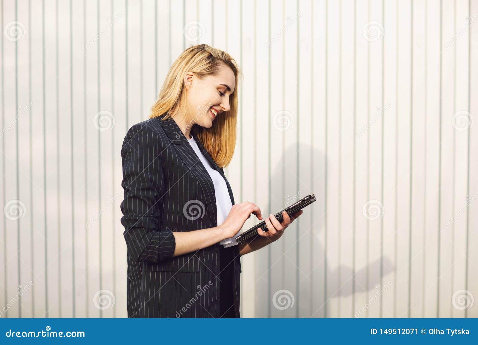 Молодая коммерсантка используя планшет, во время на открытом воздухе перерыва на чашку кофе, около офисного здания E