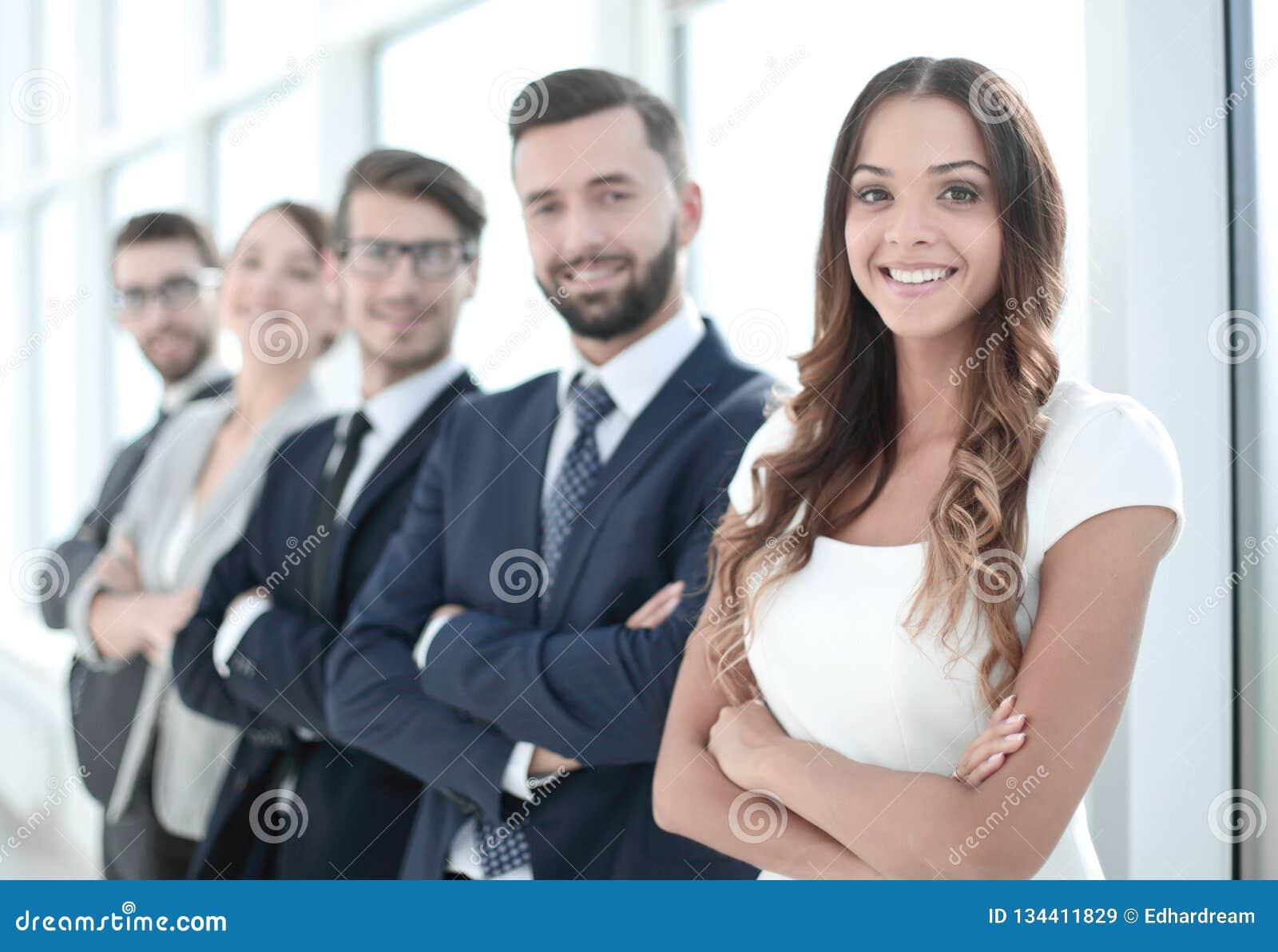 Молодая коммерсантка и команда дела стоя совместно