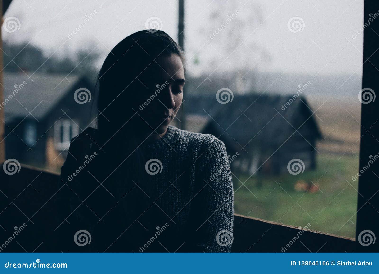 Молодая красивая девушка в деревне Модель на предпосылке деревянного дома в деревне темный свет