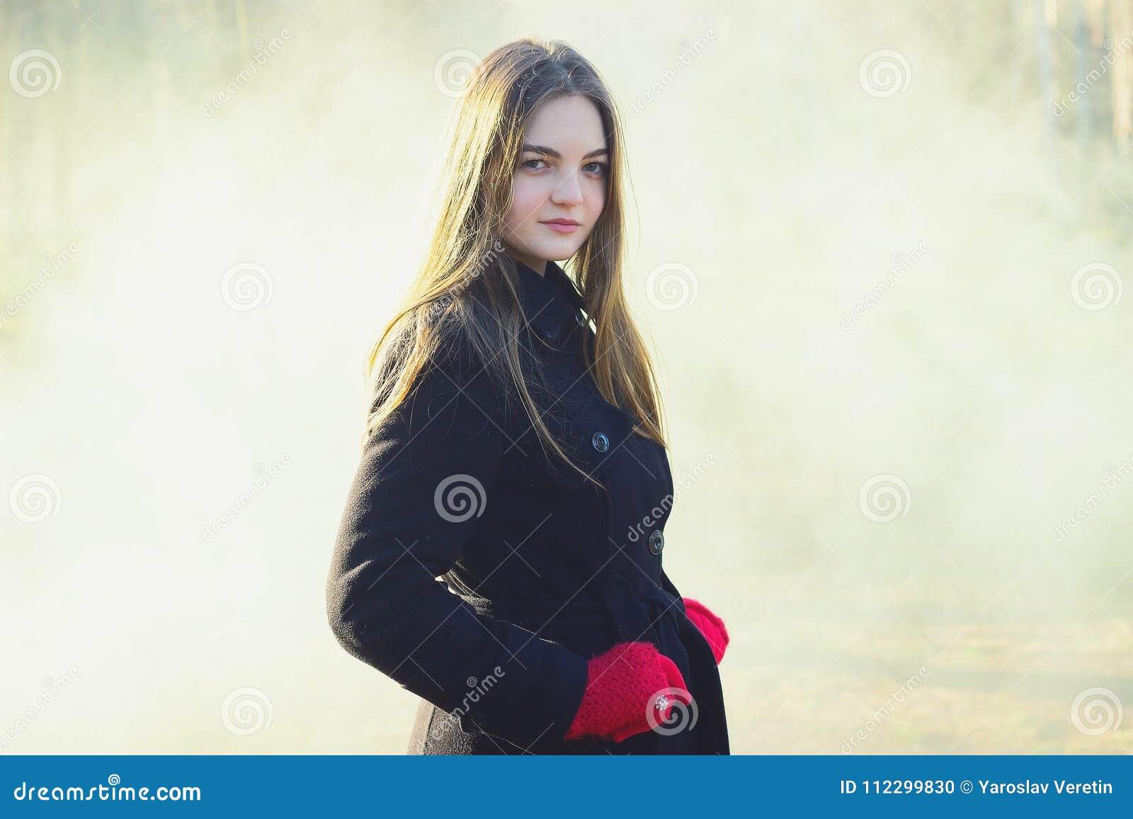 Молодая красивая девушка в перчатках черного пальто красных исследуя дым леса весны паркует