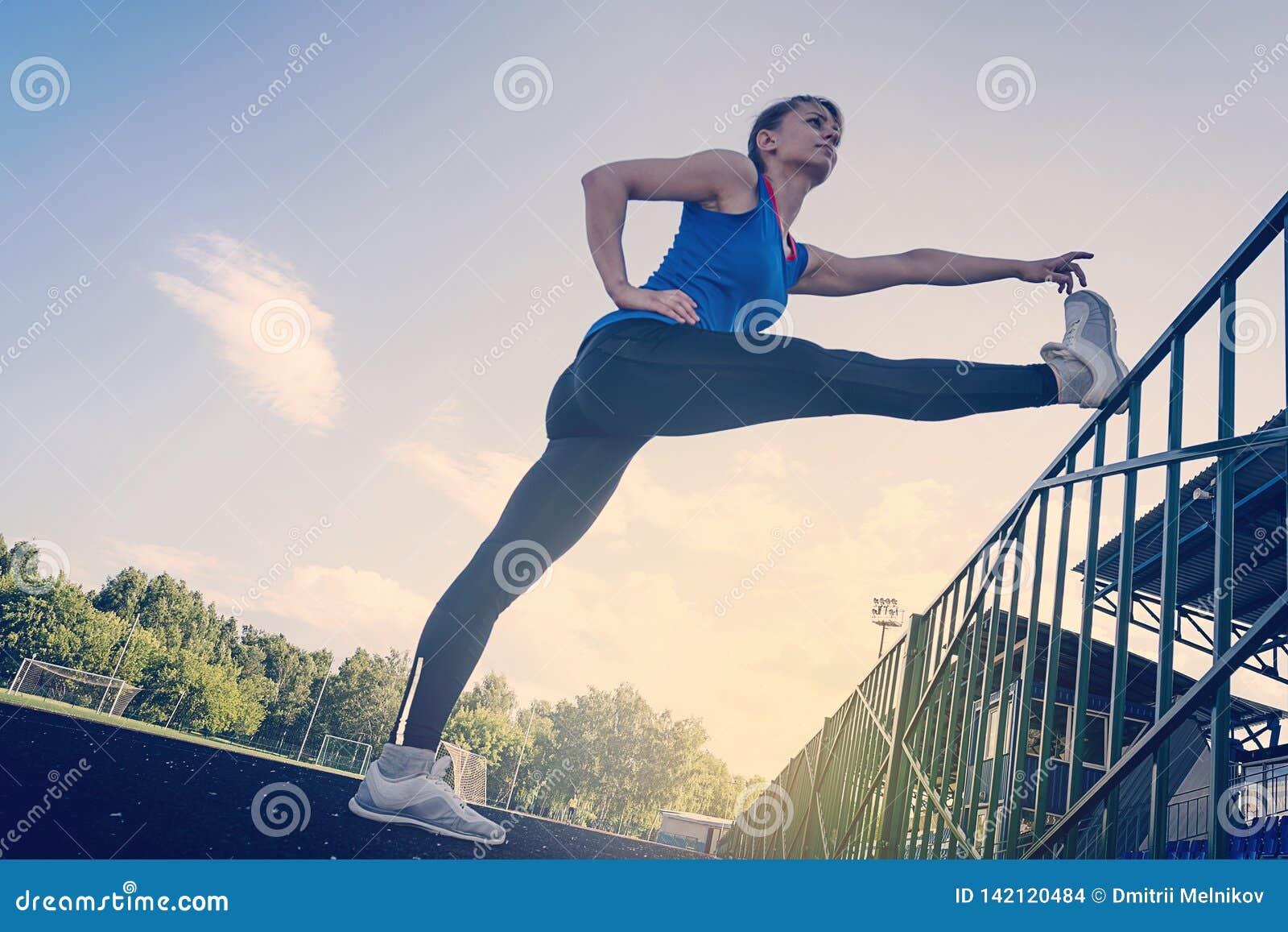 Молодая красивая девушка фитнеса делая протягивать на стадионе Спорт, концепция здравоохранения