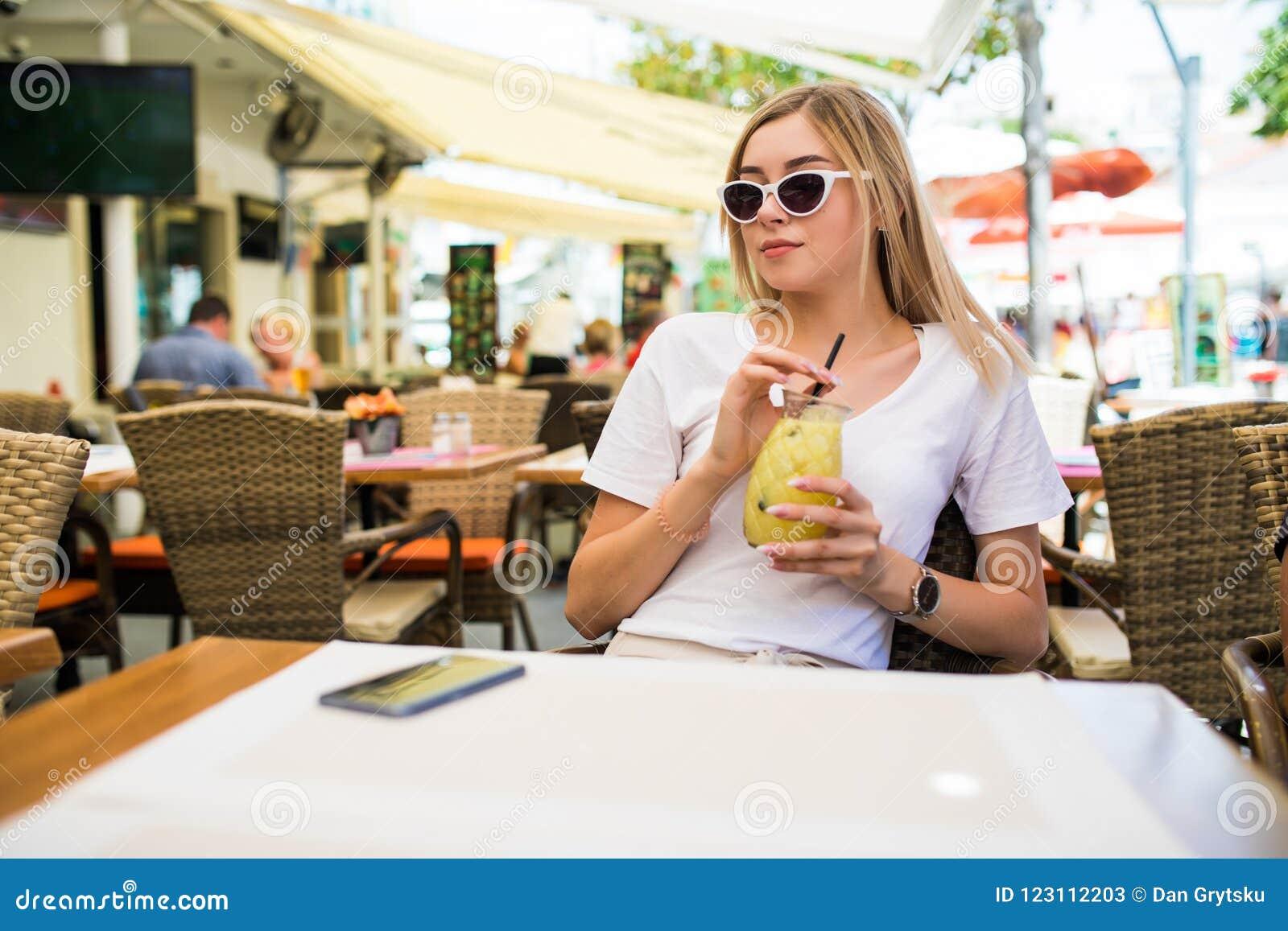 Молодая красивая женщина в круглых солнечных очках с коктейлем на террасе кафа имея потеху