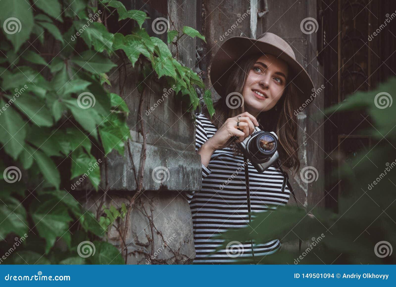 Молодая красивая женщина в шляпе фотографирует со старомодной камерой, outdoors