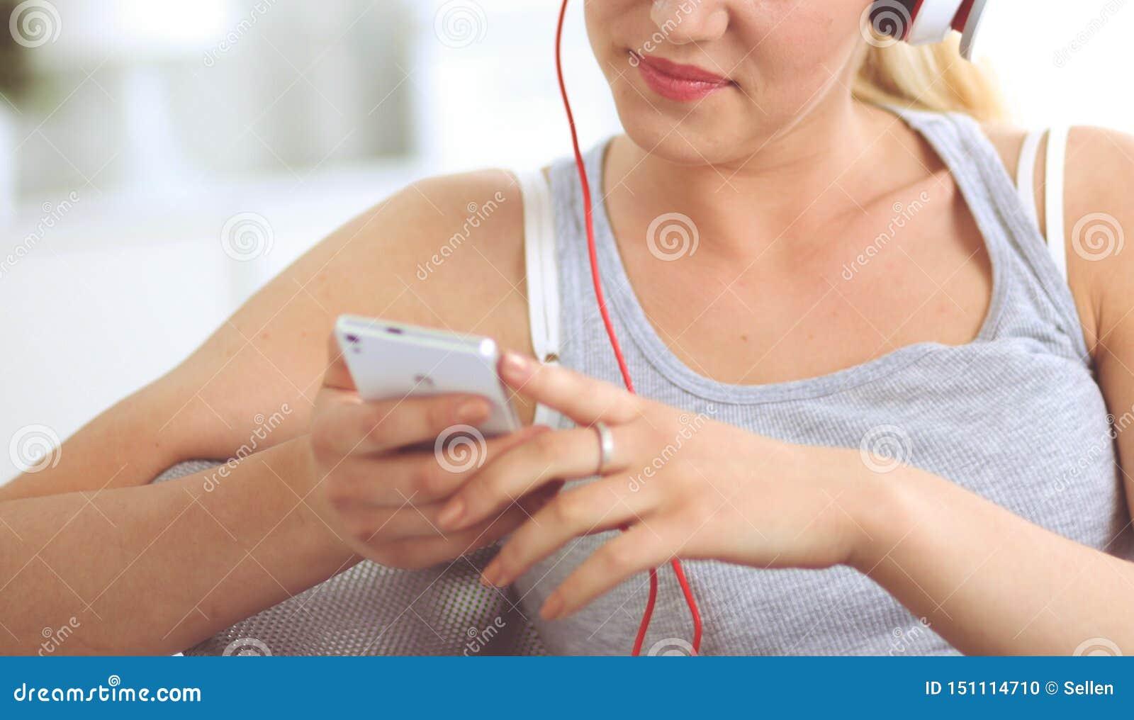 Молодая красивая женщина дома сидя на софе и слушая музыке
