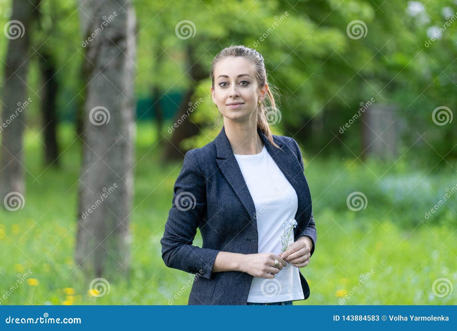 Молодая красивая женщина нося куртку дела и белые верхние улыбки, в ее руках небольшой букет незабудок