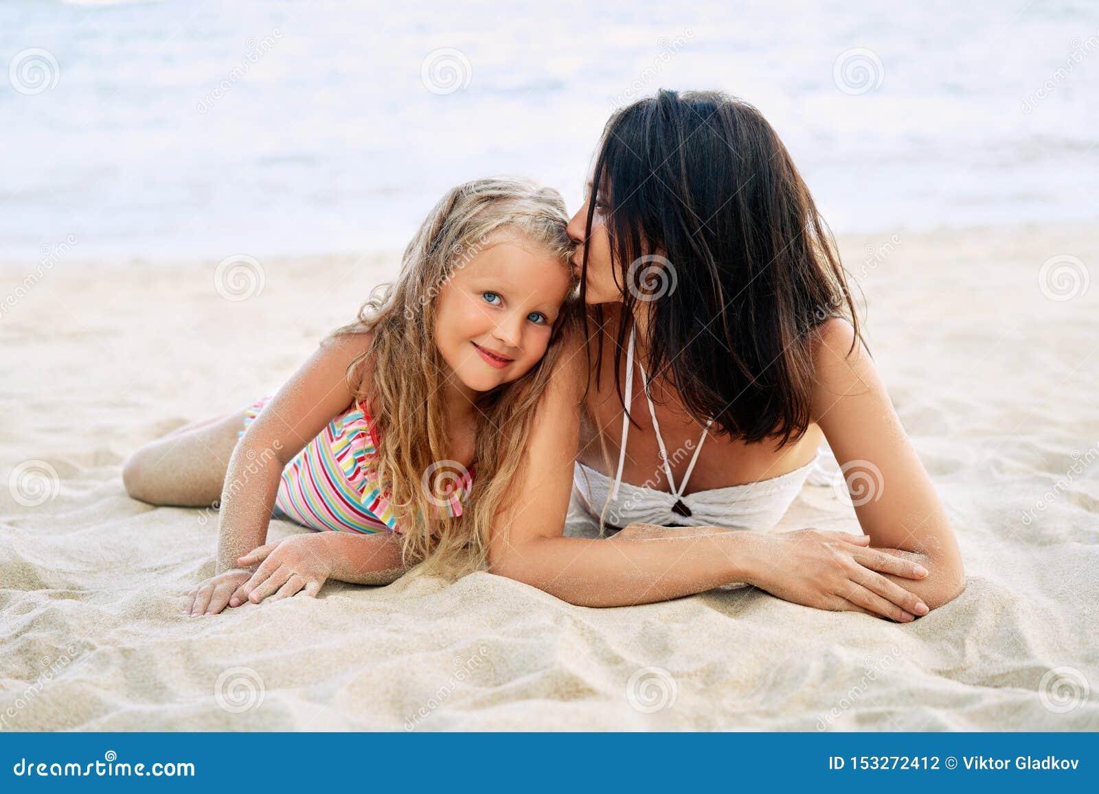 Молодая красивая женщина целуя ее маленькую дочь для того чтобы ослабить на тропическом пляже в летних каникулах