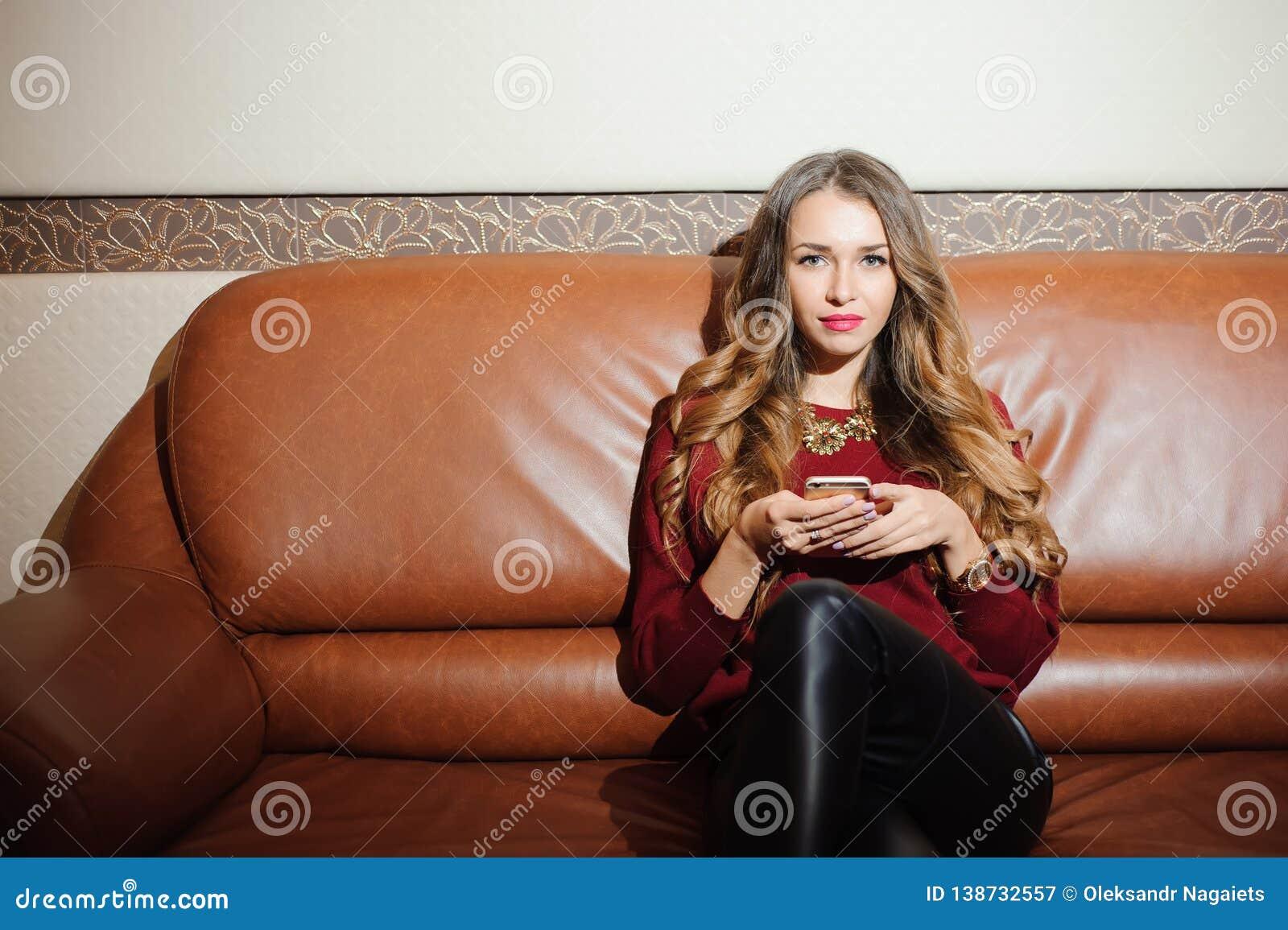 Молодая красивая коммерсантка с mobilephoneon софа