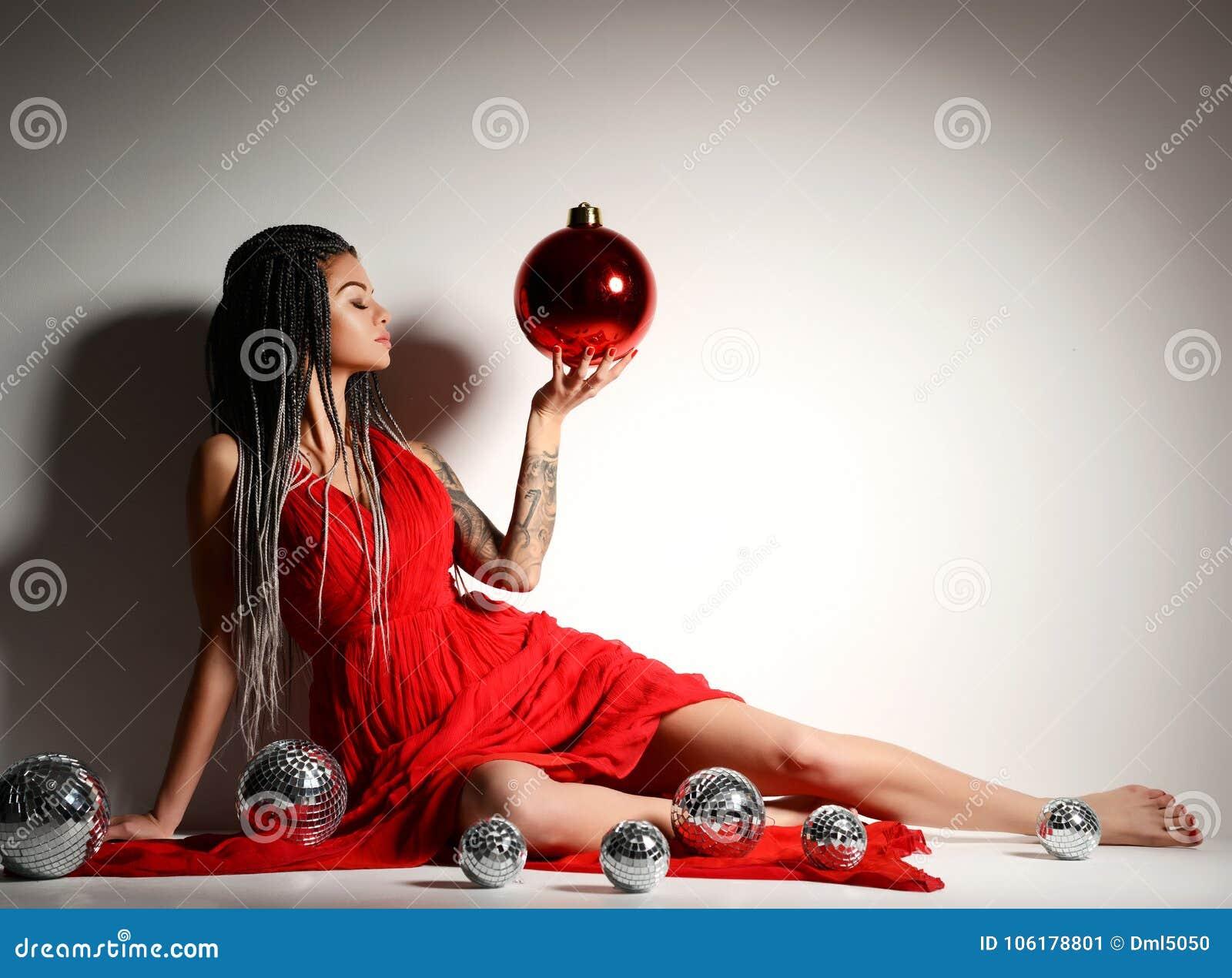 Молодая красивая сексуальная женщина в элегантном красном платье сидя в кроне золота с шариком и confetti украшения рождества
