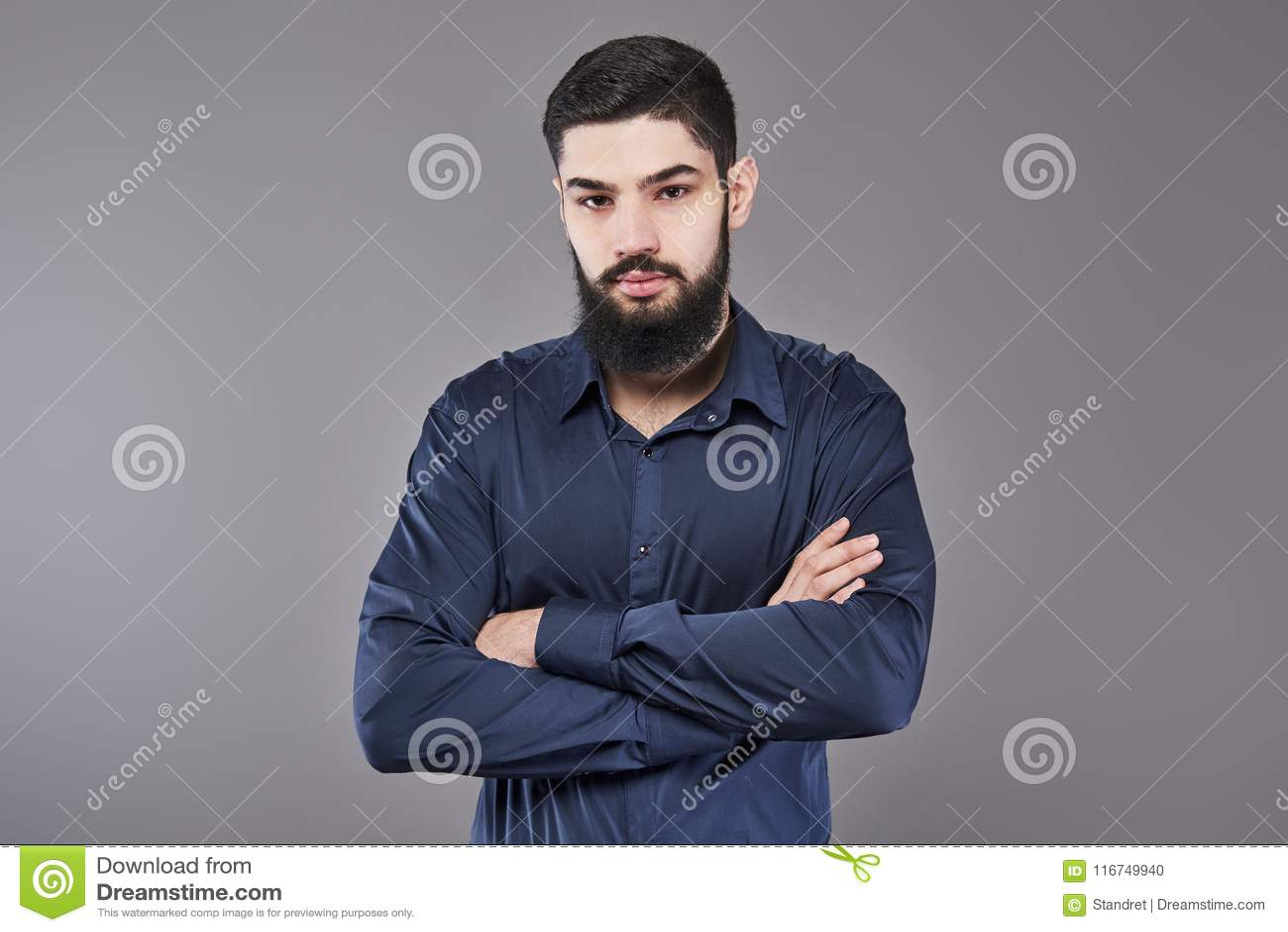 Молодая красивая склонность человека против серой стены при пересеченные оружия Серьезный молодой человек с бородой смотрит камер