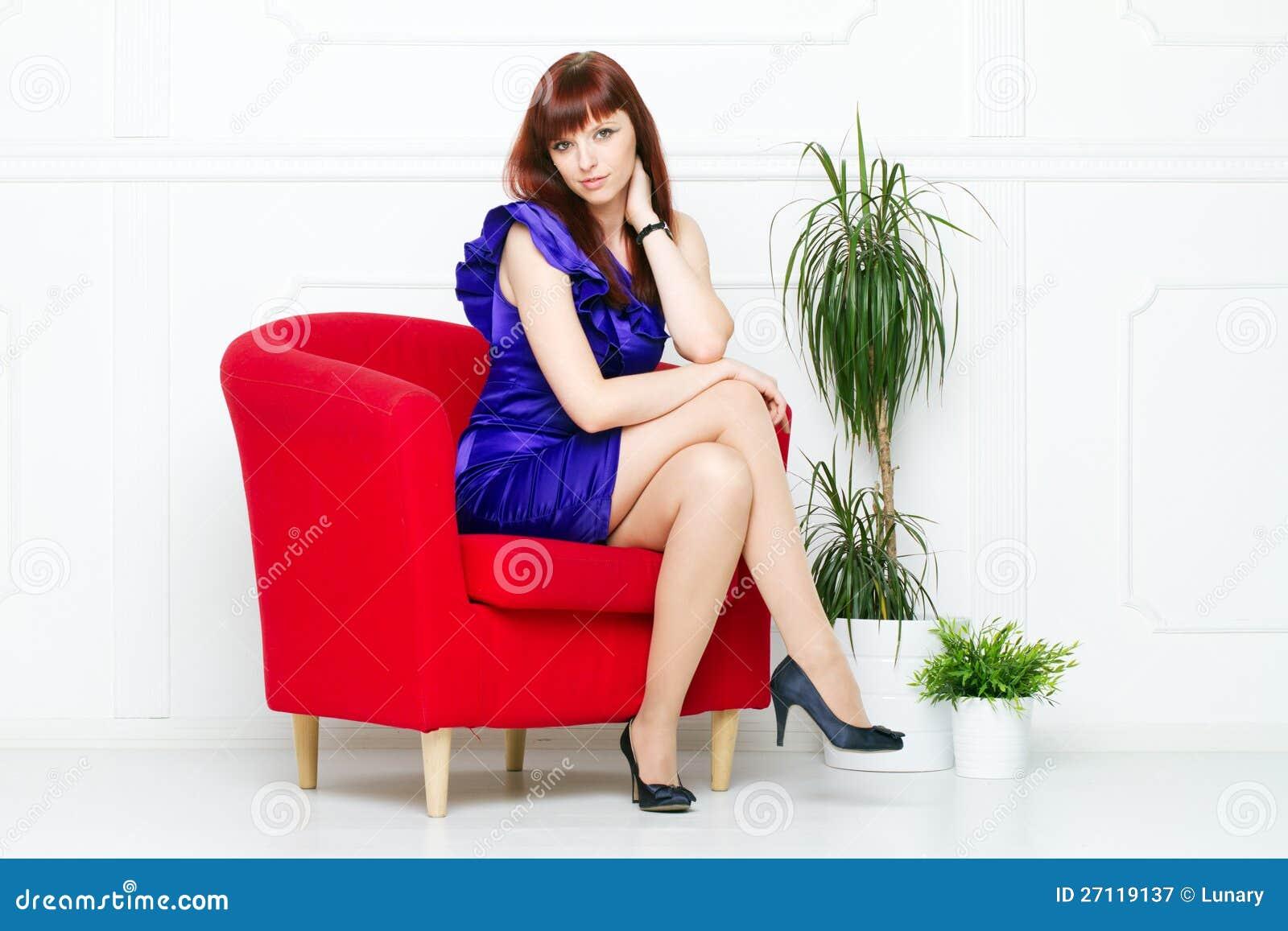 Молодая красивейшая женщина в красном стуле