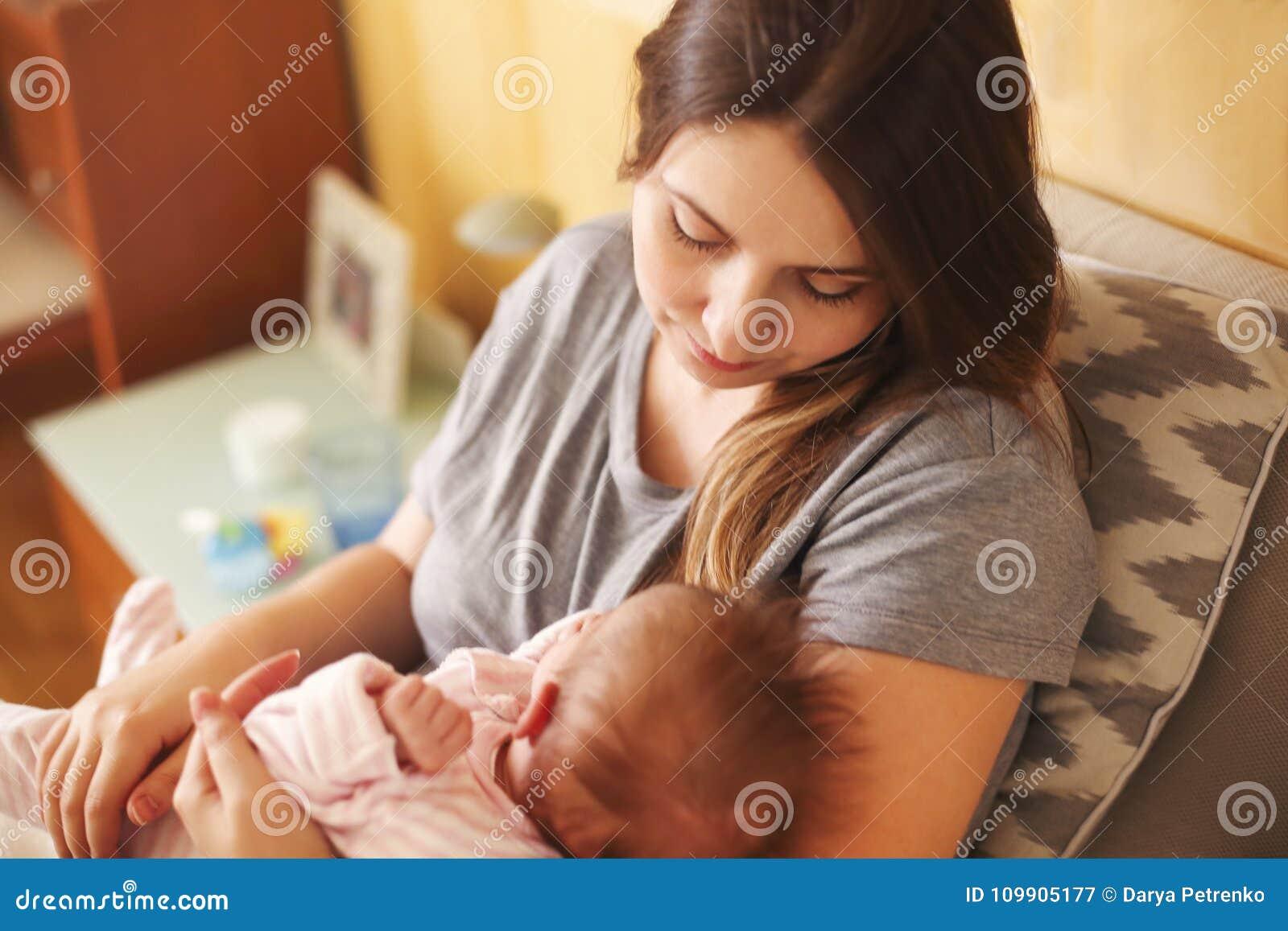 Молодая мать держа ее новорожденный ребенка Младенец ухода мамы Семья