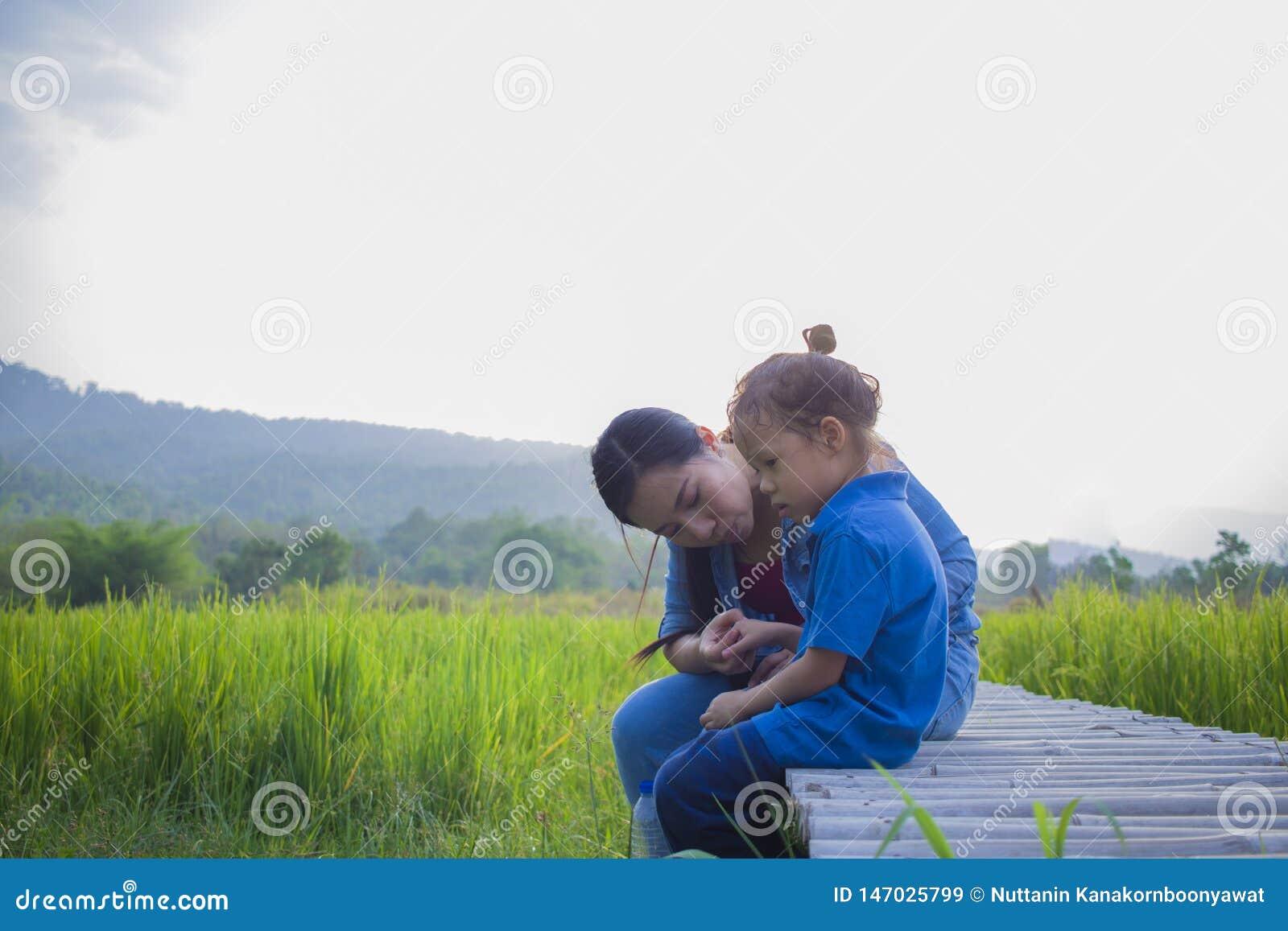 Молодая мать обнимая и успокаивая плача маленького длинного мальчика волос, азиатской матери пробуя утешить и утихомирить вниз ее