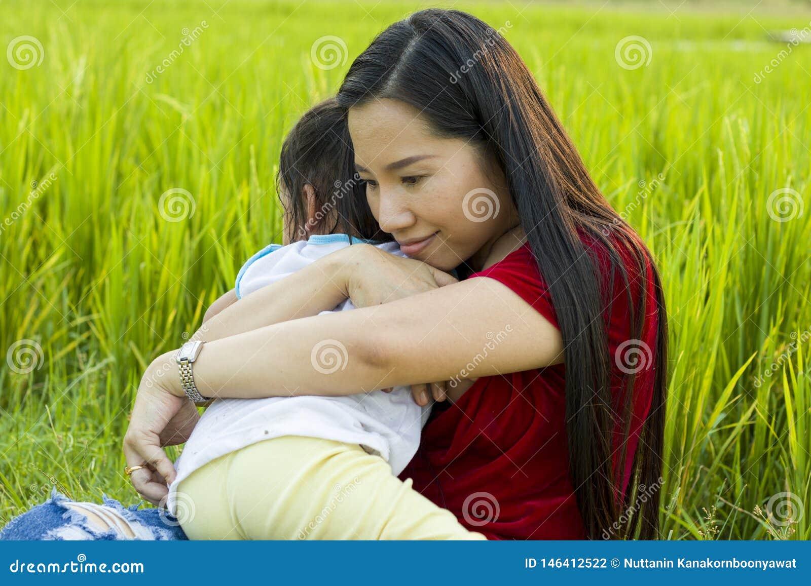 Молодая мать обнимая и успокаивая плача маленькую дочь, азиатскую мать пробуя утешить и утихомирить вниз ее плача ребенка