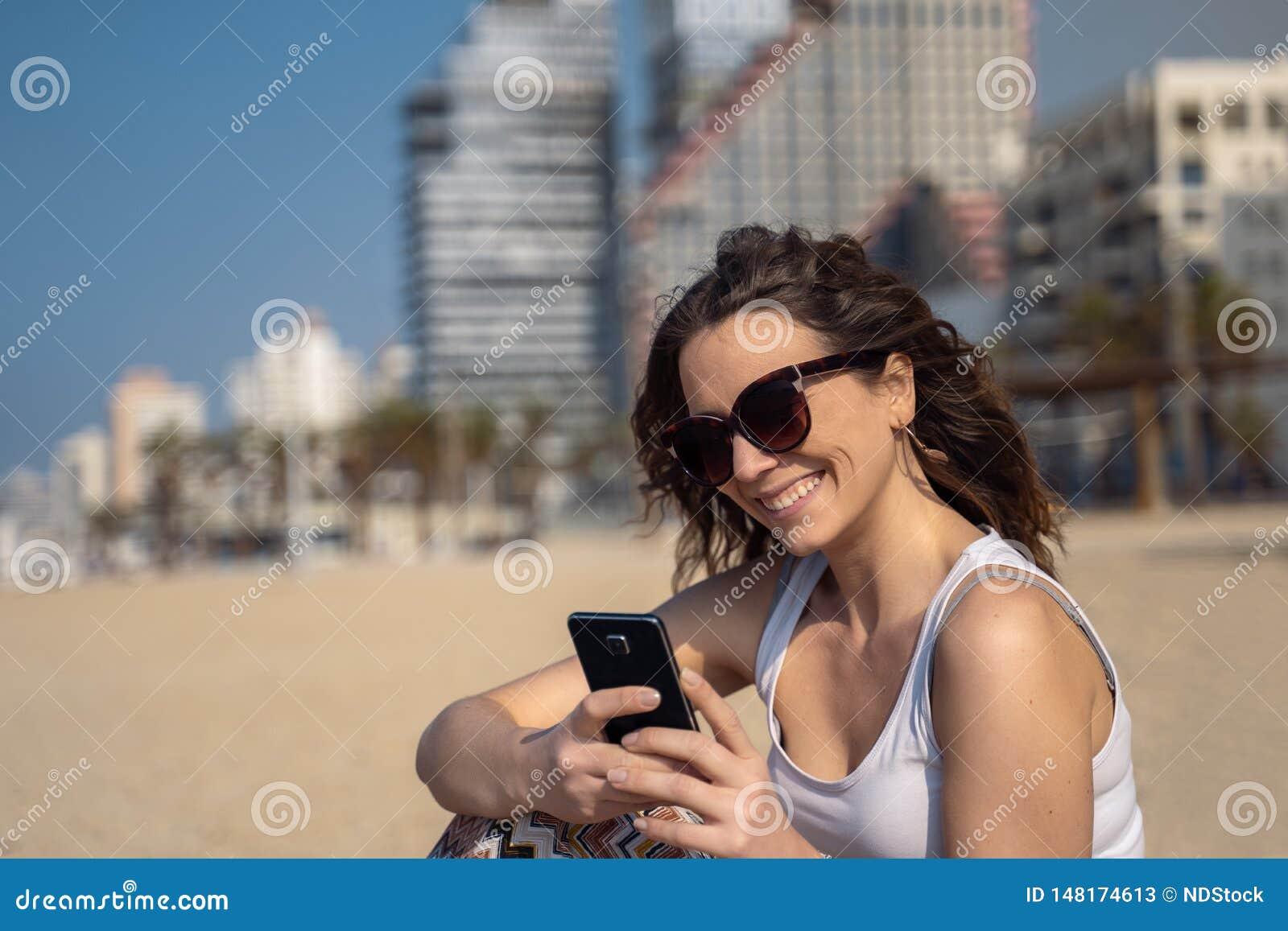 Молодая милая женщина используя смартфон на пляже Горизонт города в предпосылке