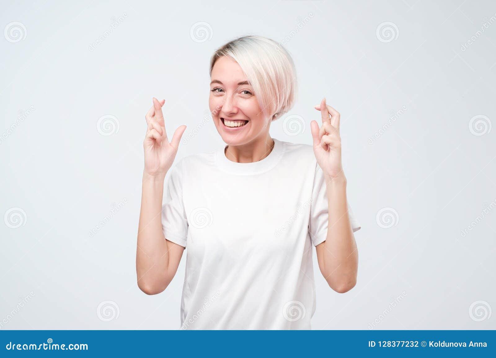 Молодая милая женщина при покрашенные волосы делая желание пересекла ее пальцы, везение, закрытые глаза, надеющийся жест
