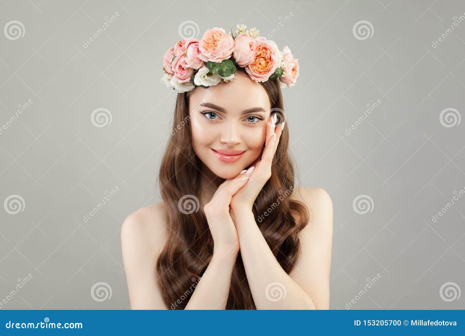 Молодая милая женщина с ясной кожей, здоровыми волосами и венком цветков