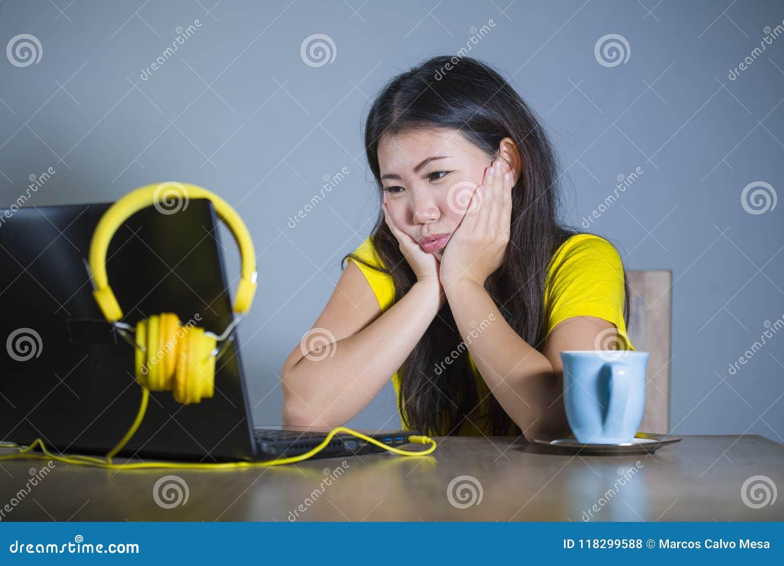 Молодая милая и пробуренная азиатская корейская девушка студента работая при портативный компьютер смотря несчастная и сонная дер