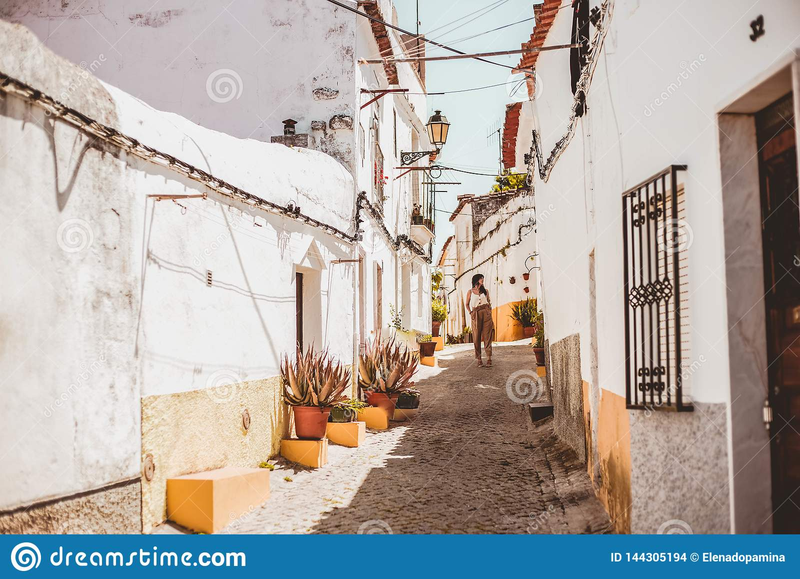 Молодая модная женщина брюнета идя вниз с улицы одного в Elvas, Португалии