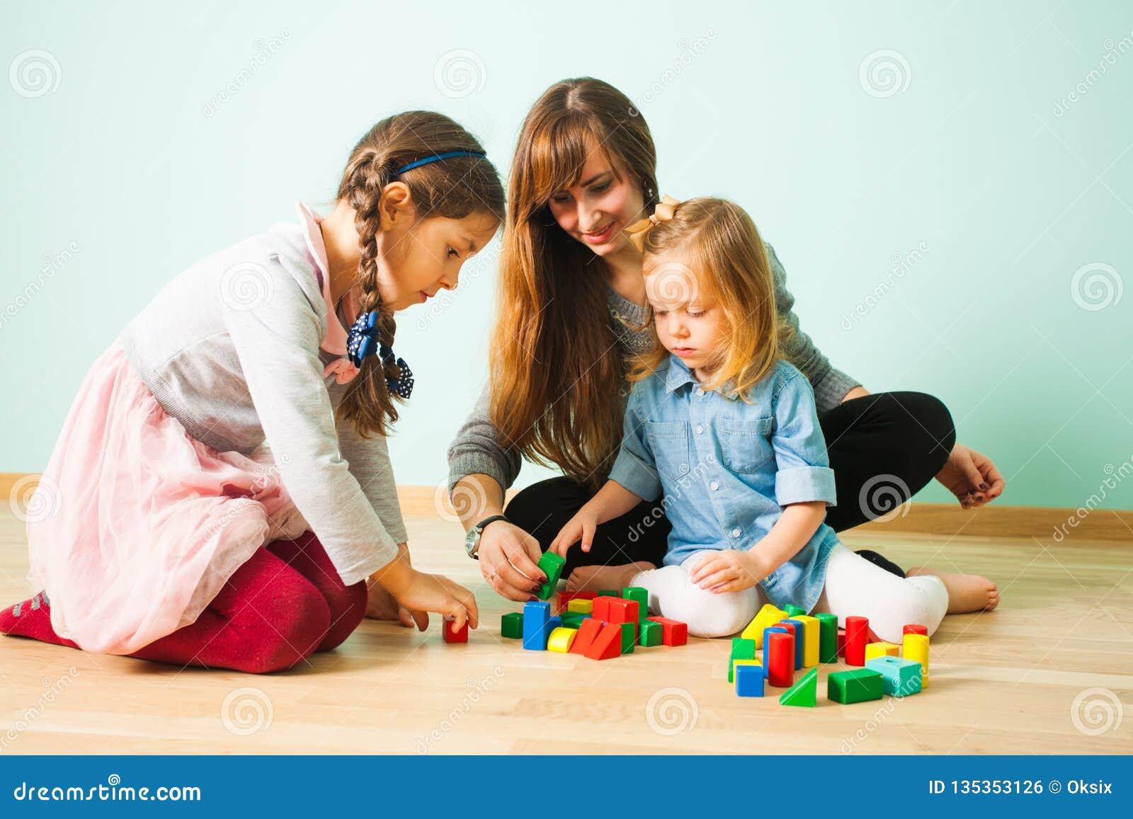 Молодая няня играя с детьми пока сидящ с детьми