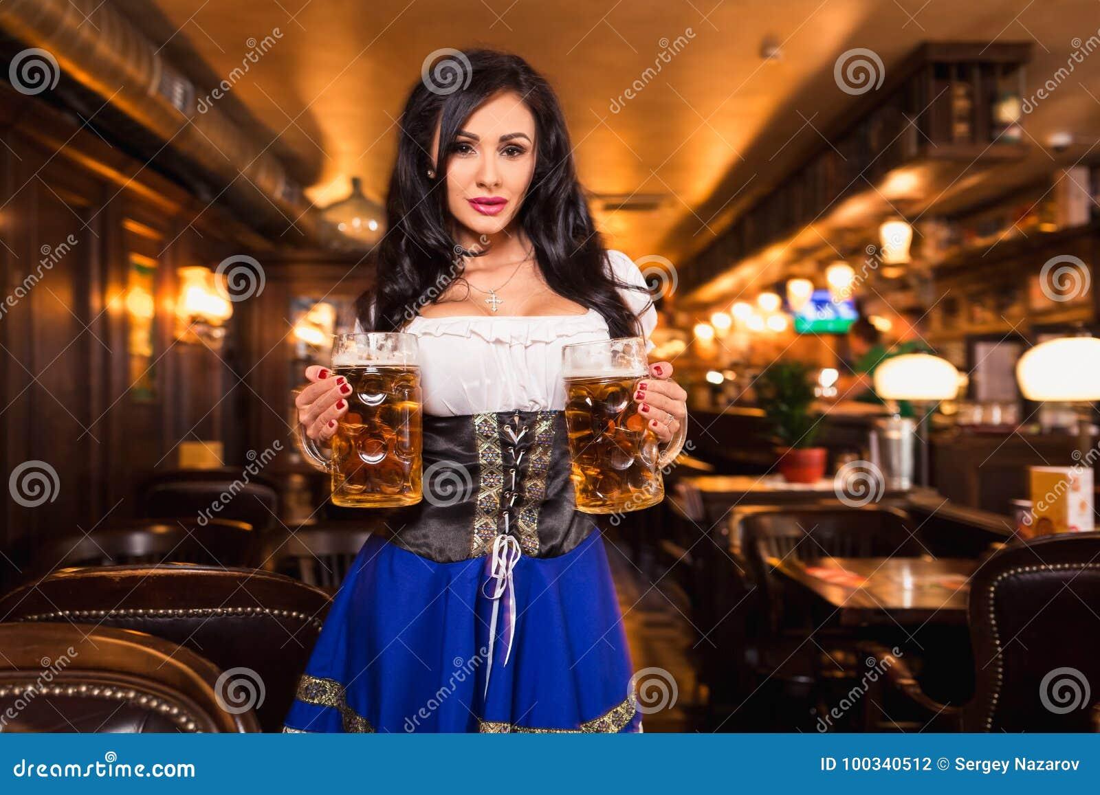 Молодая официантка приносит пиво к посетителям