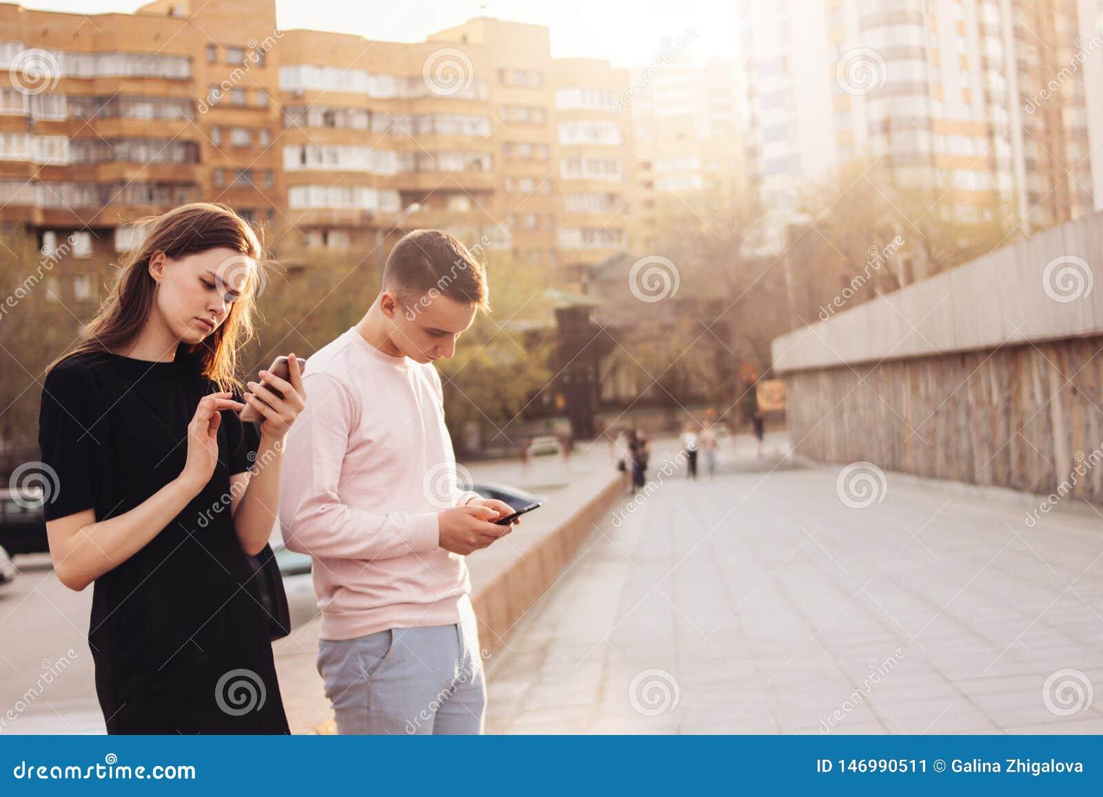 Молодая пара друзей, подростков, студентов используя мобильные телефоны на улице города