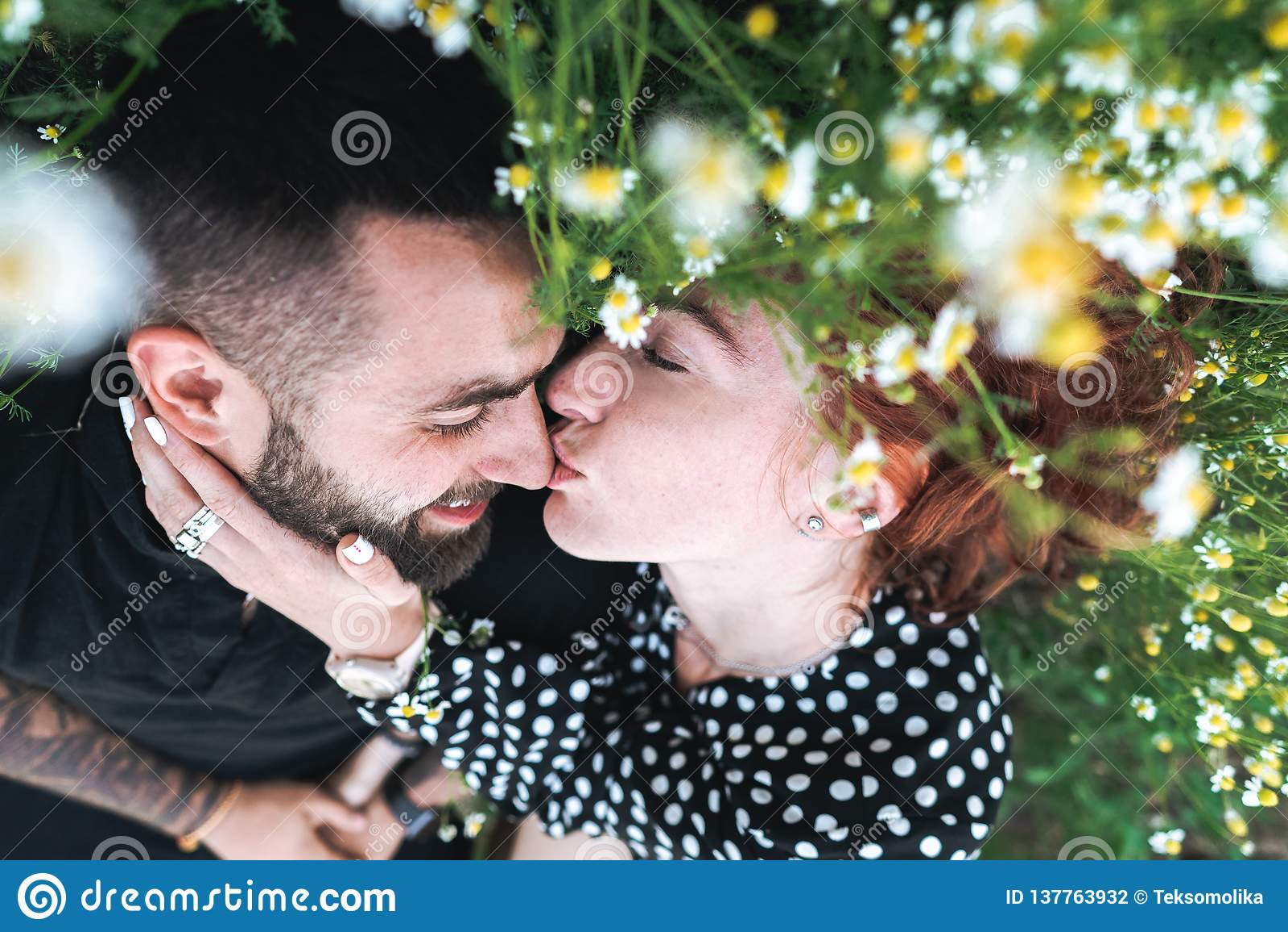 Молодая пара лежит на поле с маргаритками