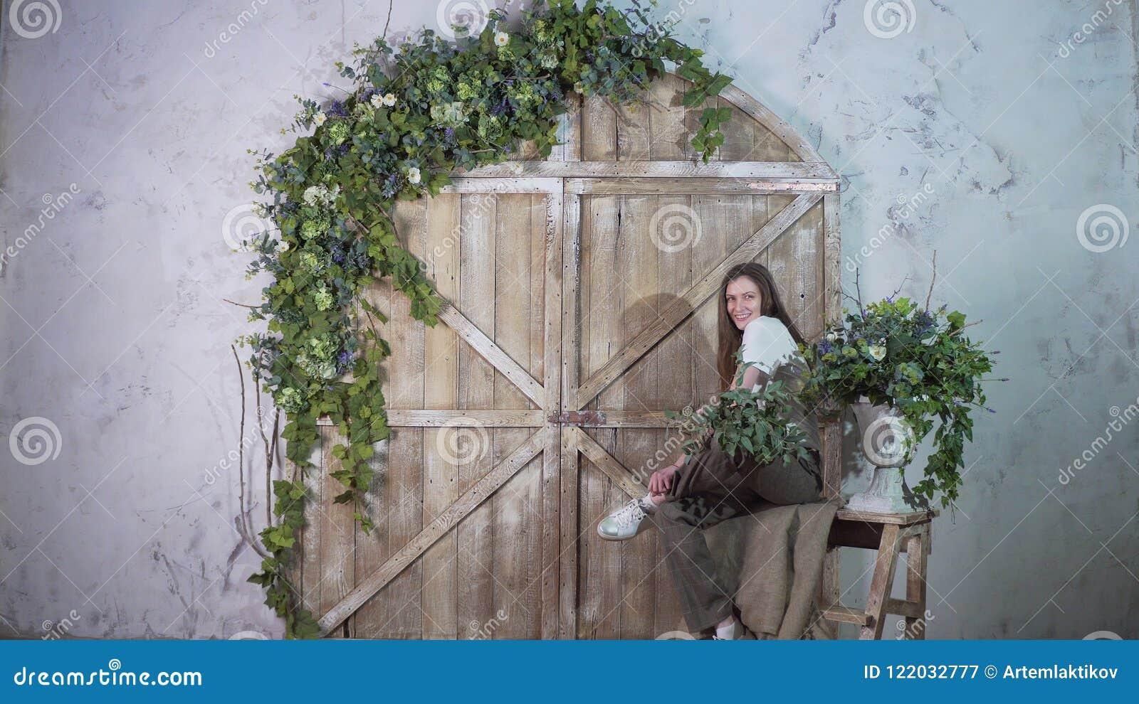 Молодая положительная девушка сидит на винтажной лестнице и смотрит в камеру
