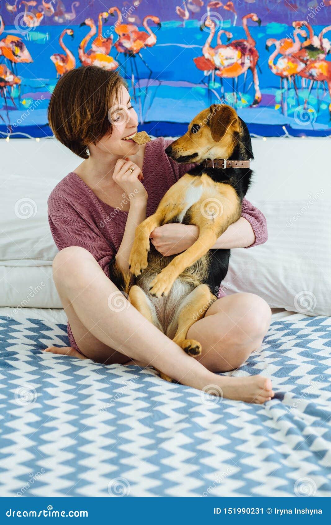 Молодая положительная женщина играя с собакой дома внутренней Смешное женское держа печенье во рте и обнимать ее собаку дворняжкы
