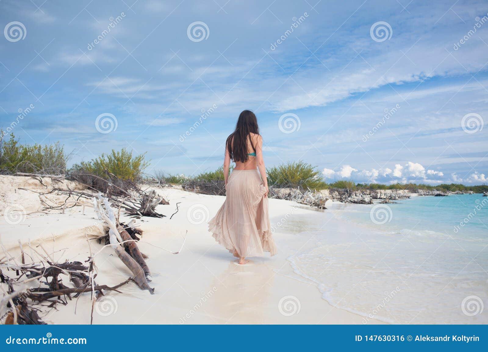 Молодая привлекательная женщина в бикини и длинной юбке Красивая девушка наслаждается солнцем лета