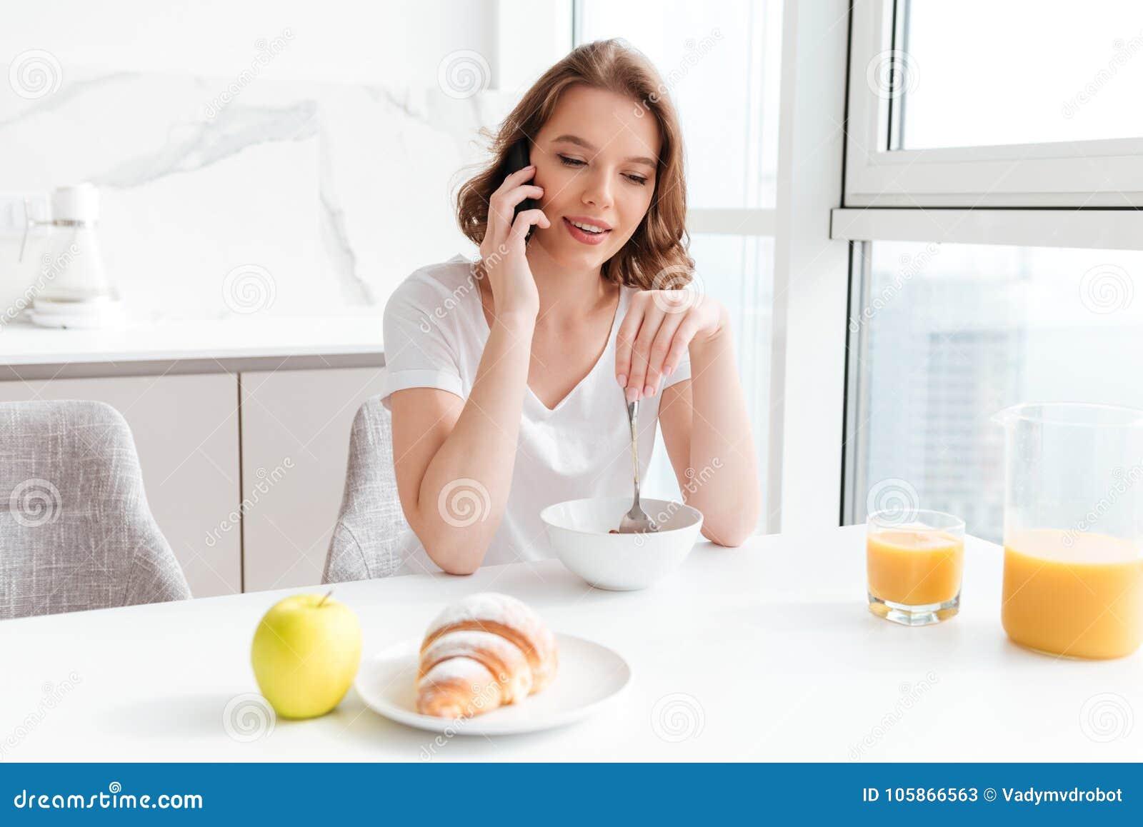 Молодая привлекательная женщина говоря на мобильном телефоне пока имеющ brea