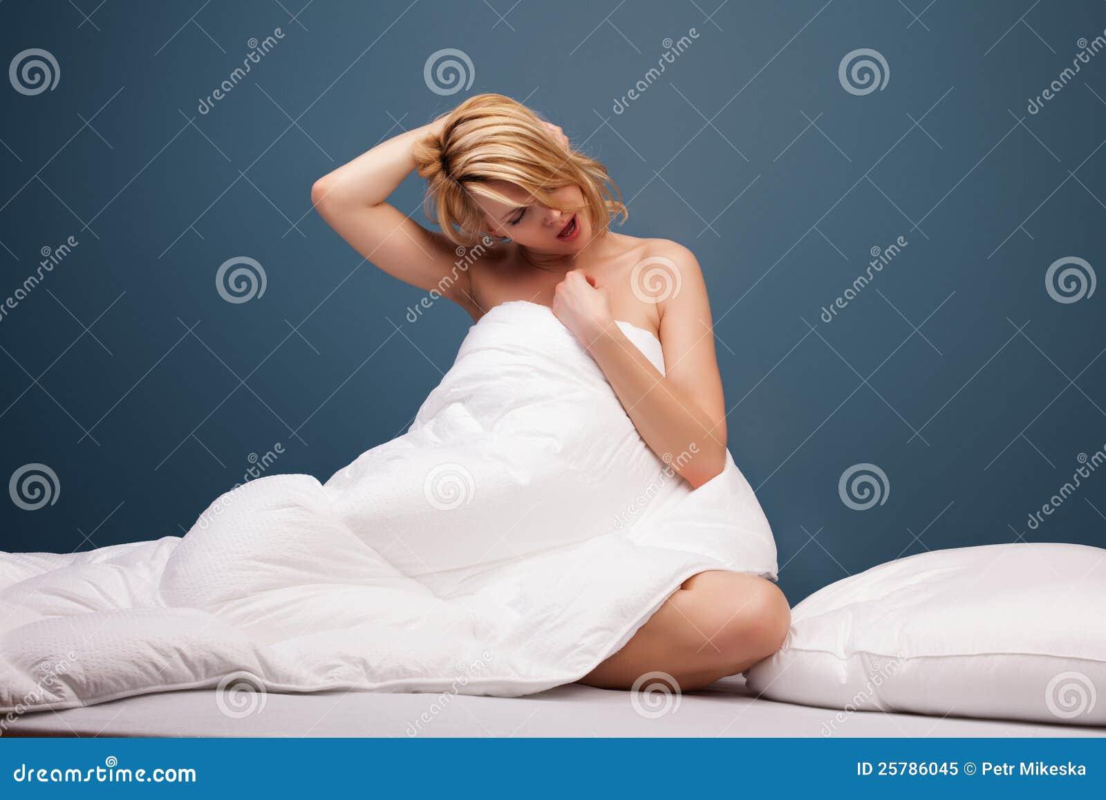 Молодая привлекательная женщина зевая в кровати
