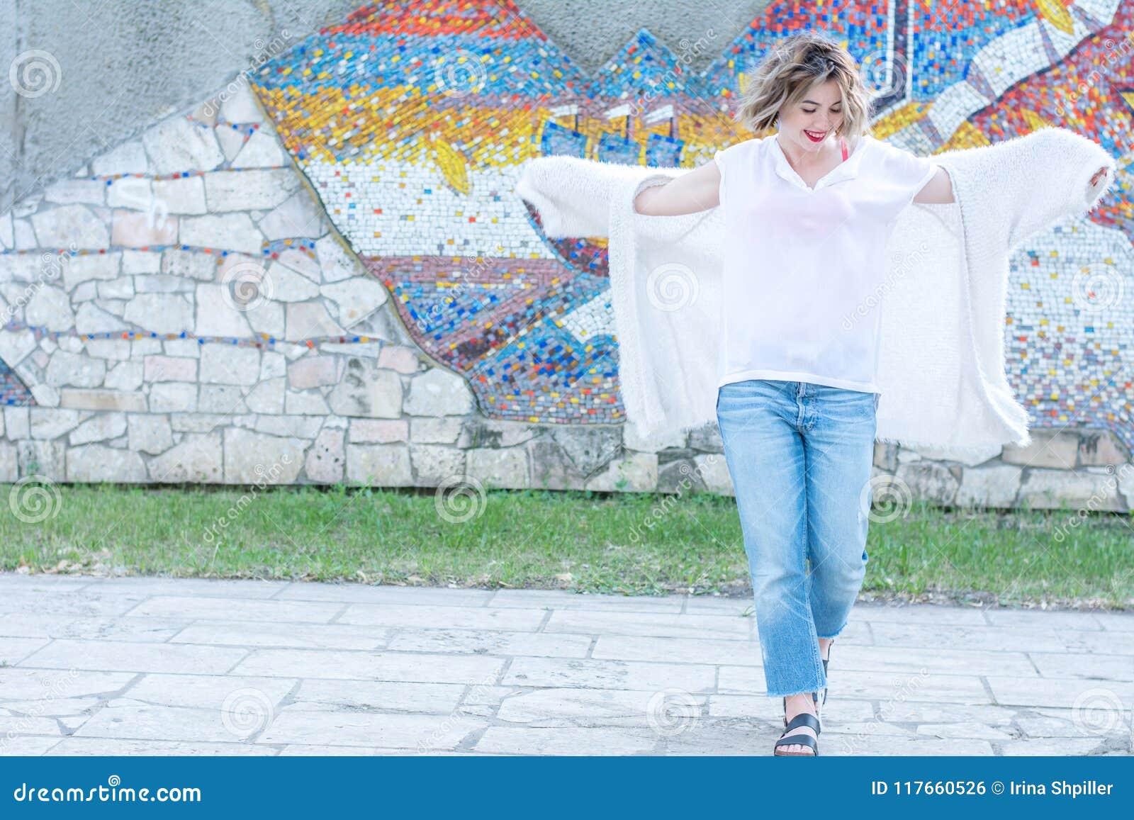Молодая привлекательная женщина с красными губами в белый представлять вскользь одежд идя в улице