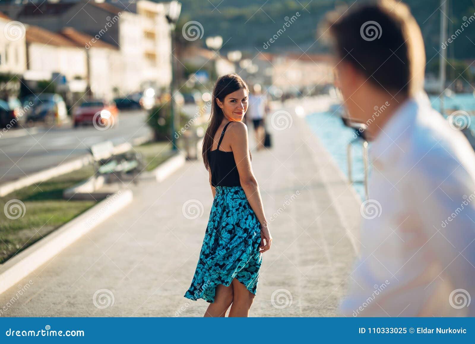 Молодая привлекательная женщина flirting с человеком на улице Flirty усмехаясь женщина смотря назад на красивом человеке Женская