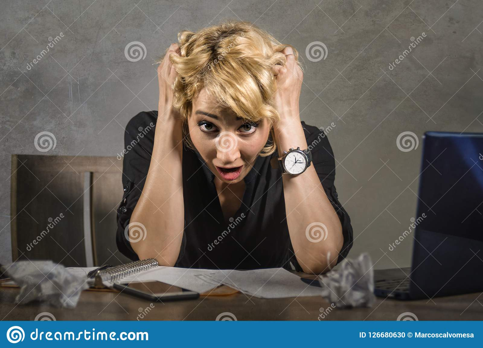 Молодая привлекательная и отчаянная бизнес-леди работая при портативный компьютер сидя на больном стола офиса кричащем и сокрушан
