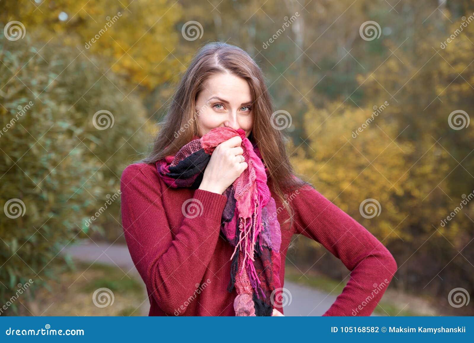 Молодая привлекательная рыжеволосая девушка идя в flirtati парка осени