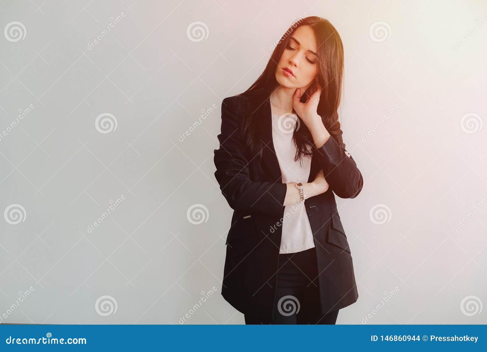 Молодая привлекательная эмоциональная девушка в одеждах дел-стиля на простой белой предпосылке в офисе или аудитории