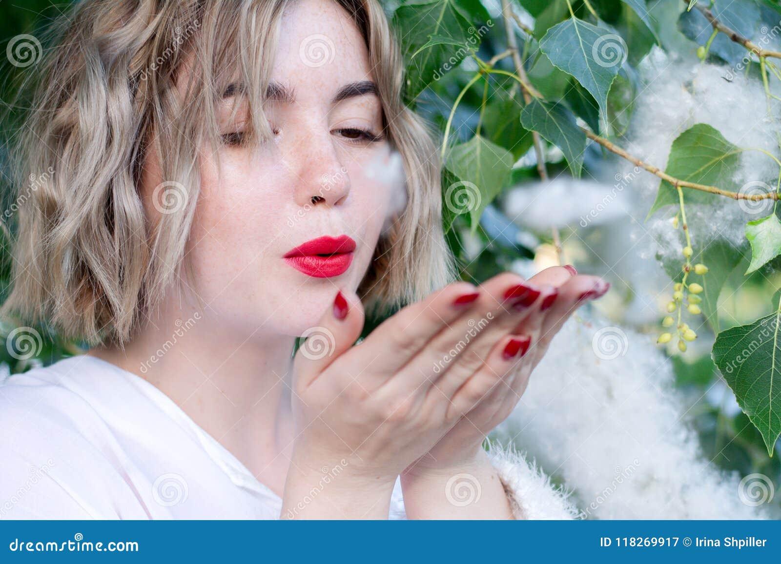 Молодая привлекательная freckled девушка дует приполюсный пушок, красные губы