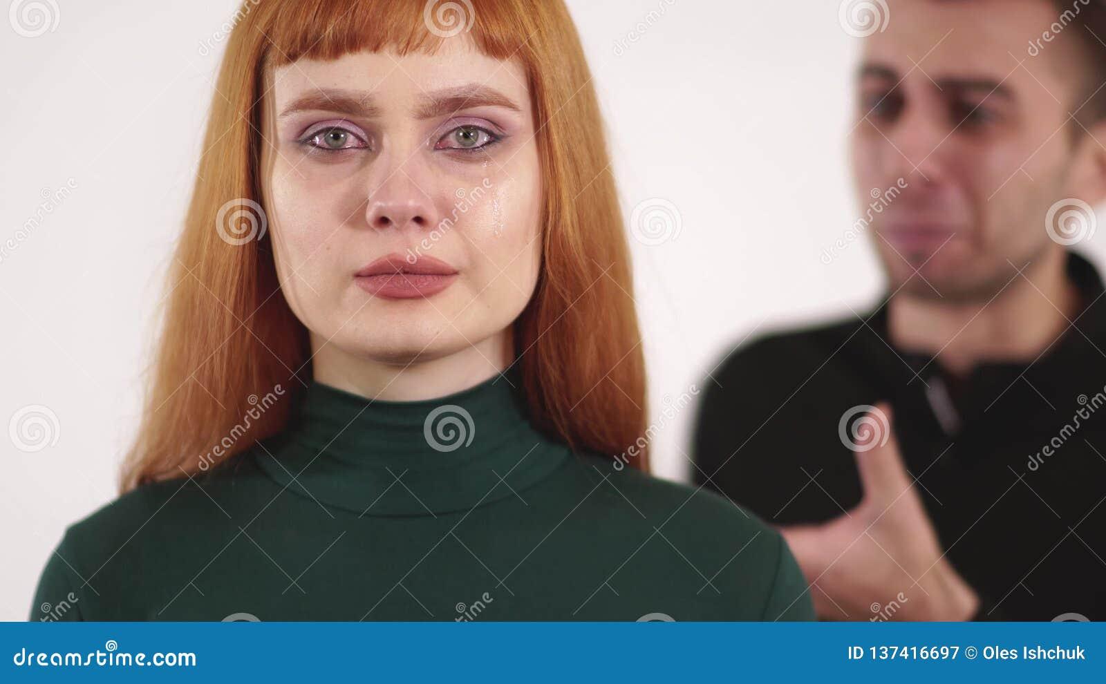 Молодая расстроенная женщина с красными длинными волосами плачет и молодой сердитый человек выкрикивает за ее задней частью акции видеоматериалы