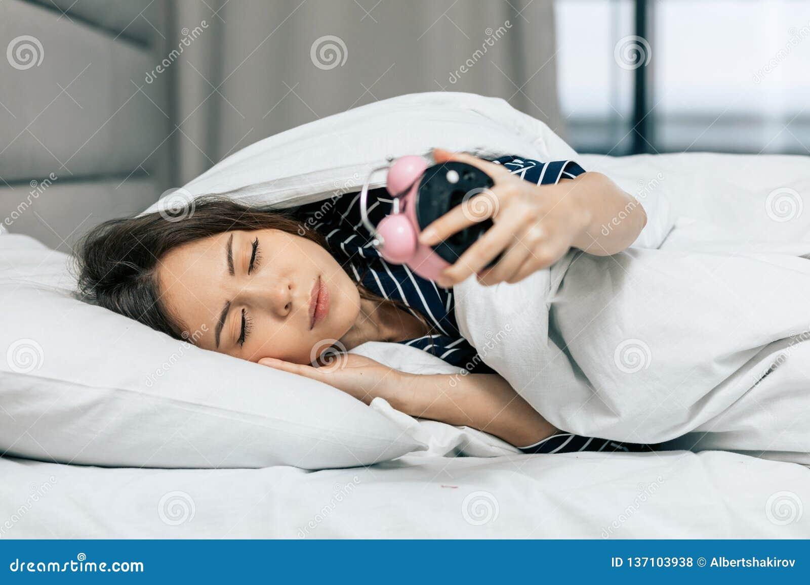 Молодая спать женщина смотря будильник в спальне