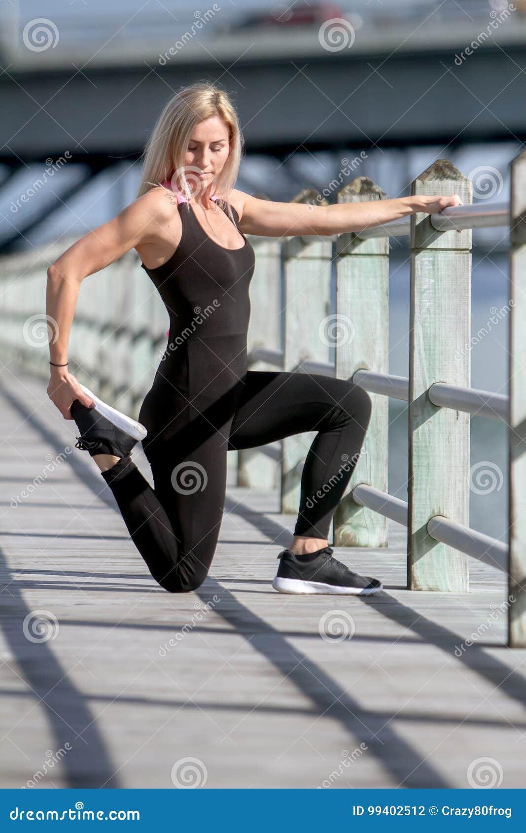 Молодая счастливая белокурая девушка делая спорт в городе