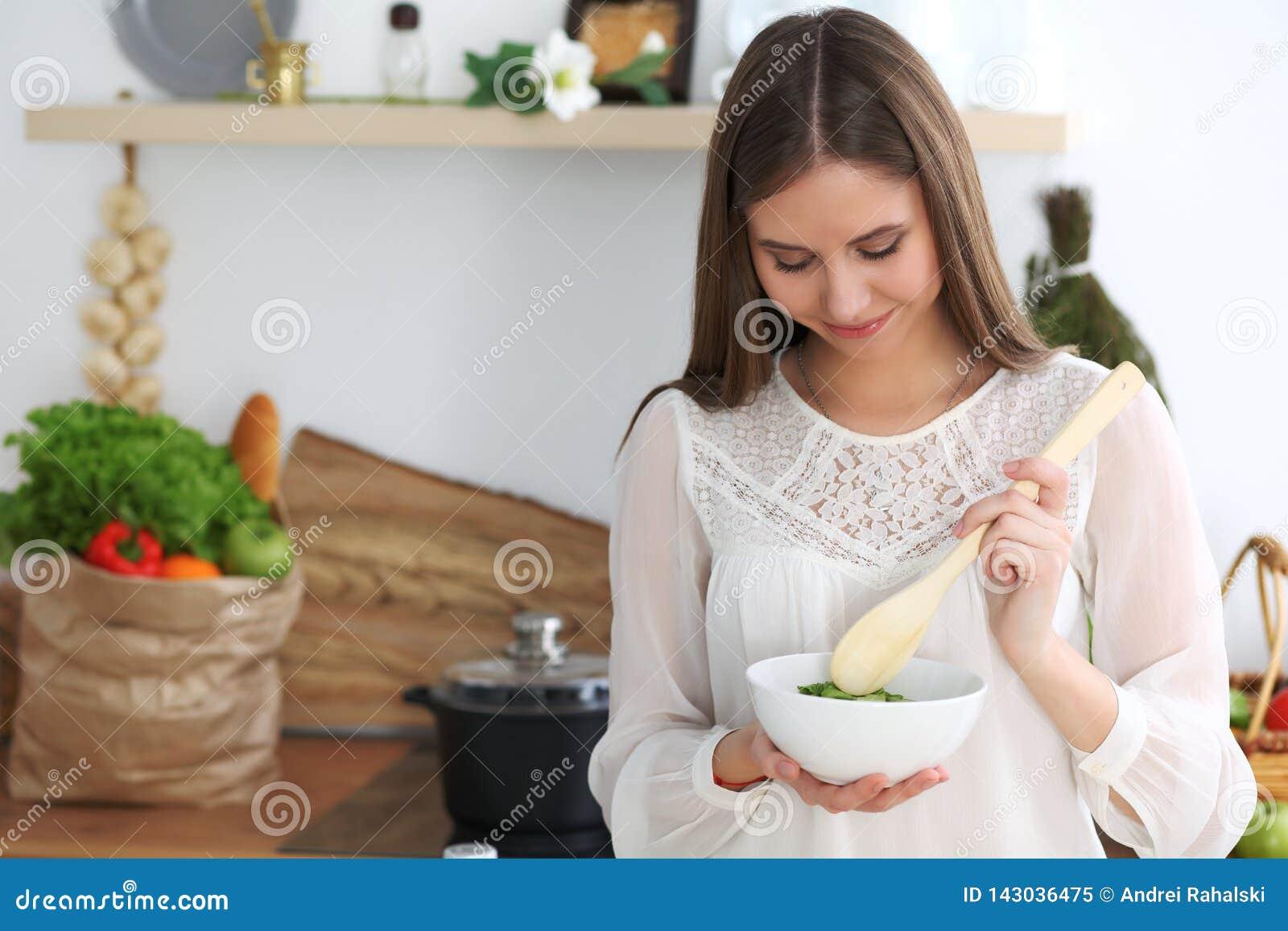 Молодая счастливая женщина варя в кухне Здоровая еда, образ жизни и кулинарные концепции Доброе утро начинает со свежим