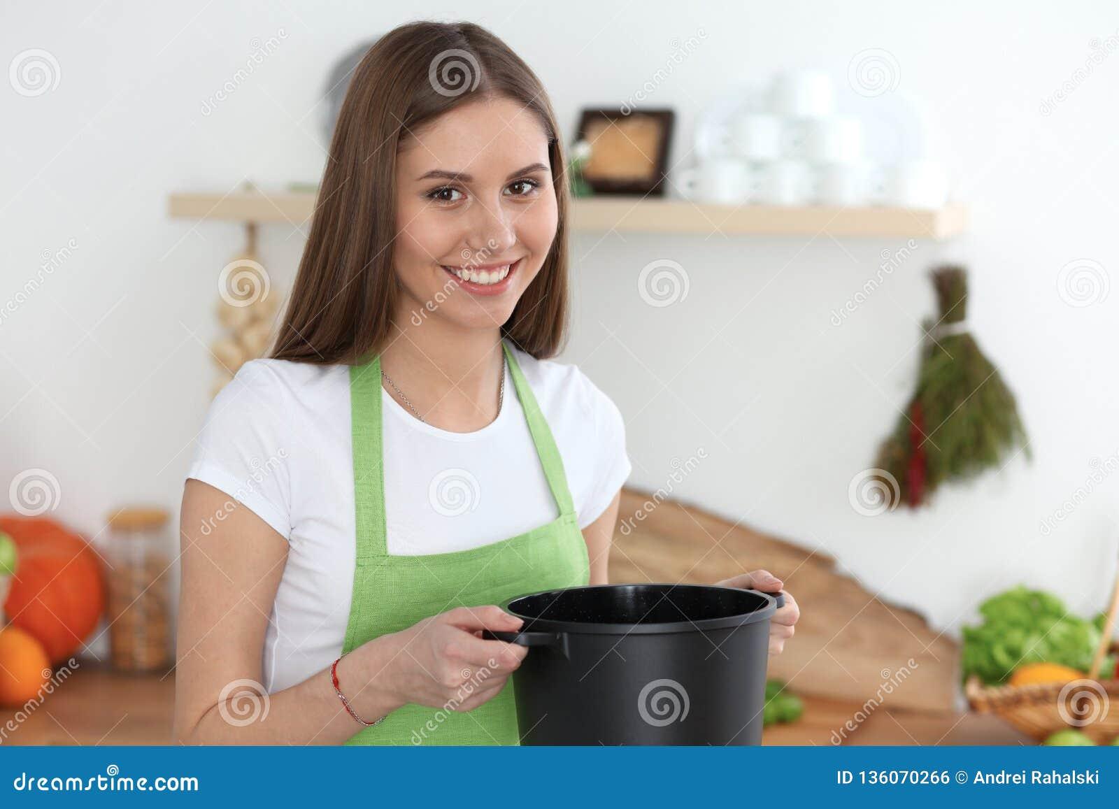 Молодая счастливая женщина варя суп в кухне Здоровая еда, образ жизни и кулинарная концепция студент девушки сь