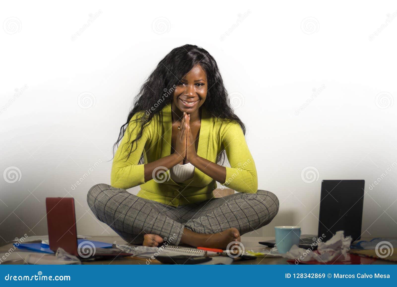 Молодая счастливая и привлекательная Афро-американская бизнес-леди делая йогу сидя на столе офиса грязном вполне усмехаться обраб