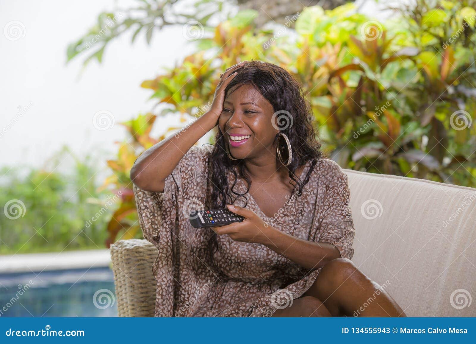 Молодая счастливая и привлекательная элегантная черная Афро-американская женщина смотря регулятор удерживания телевидения иметь п