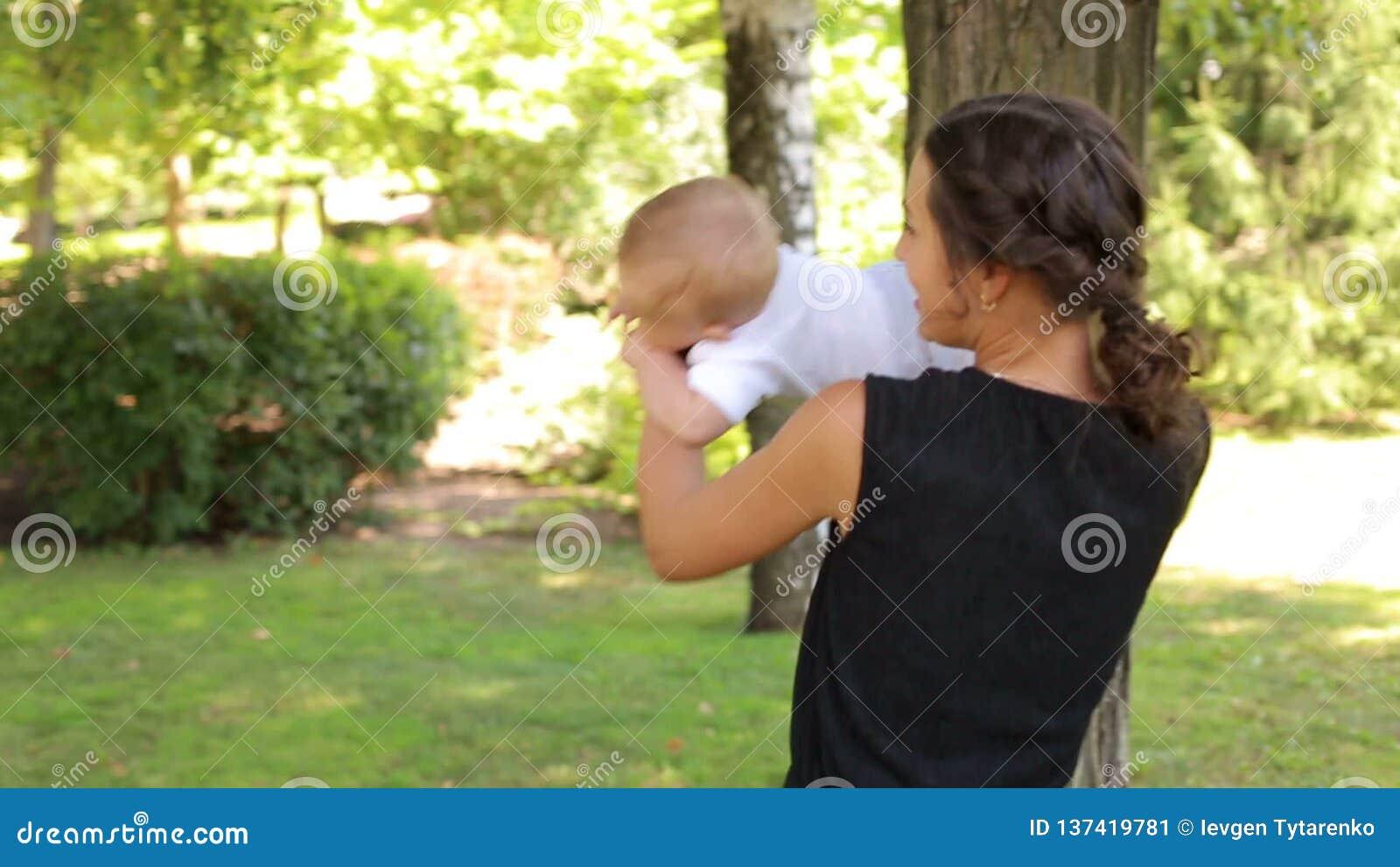 Молодая счастливая мать идет с ее newborn сыном в парке летом акции видеоматериалы