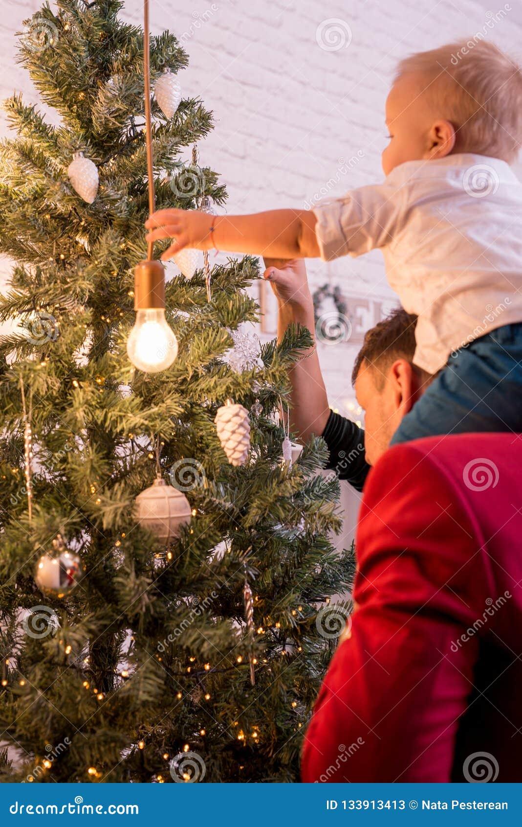 Молодая счастливая семья одевая рождественскую елку задний взгляд