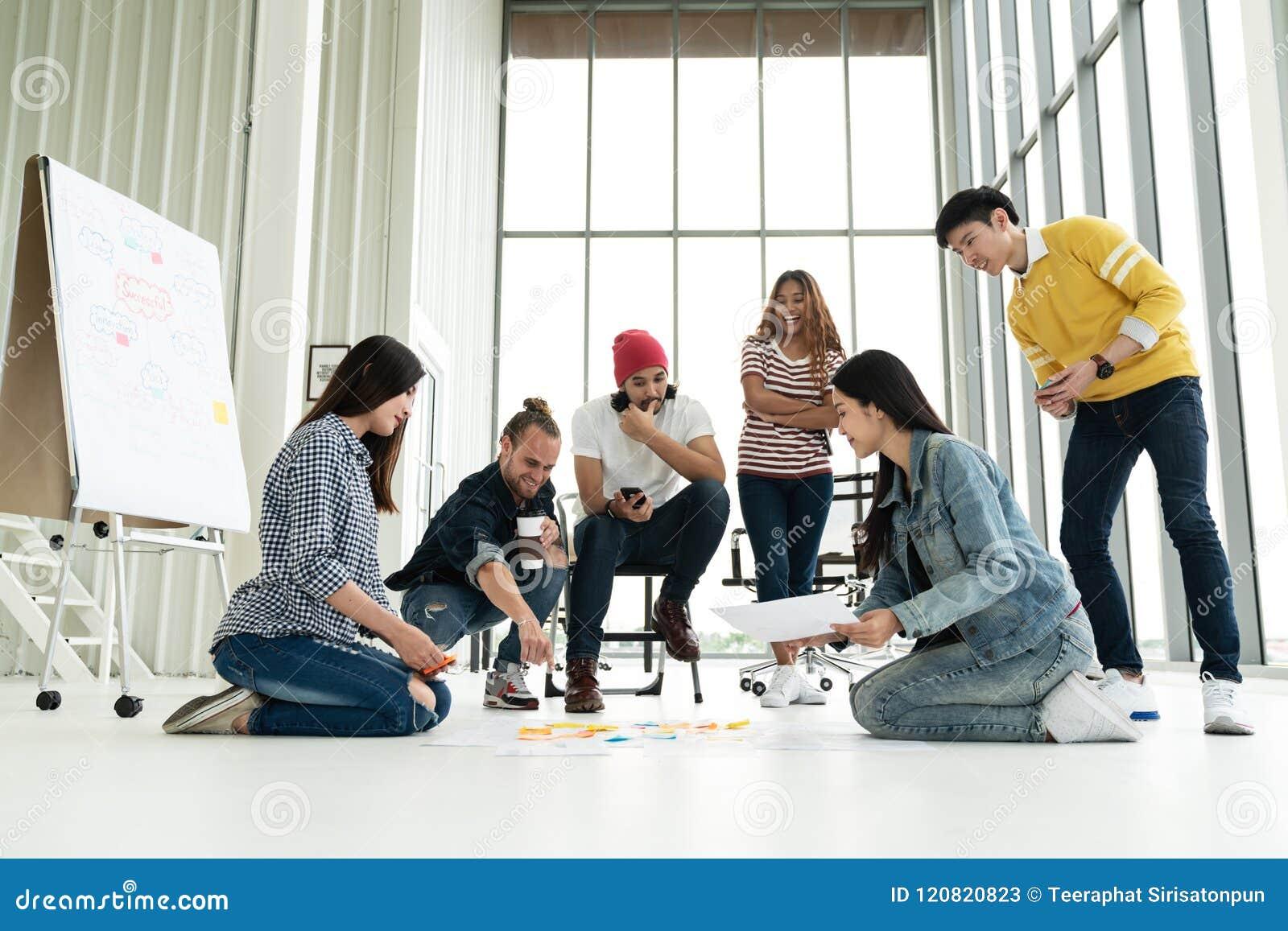 Молодая творческая разнообразная групповая встреча и смотреть план проекта положенный вне на пол обсуждают или коллективно обсужд