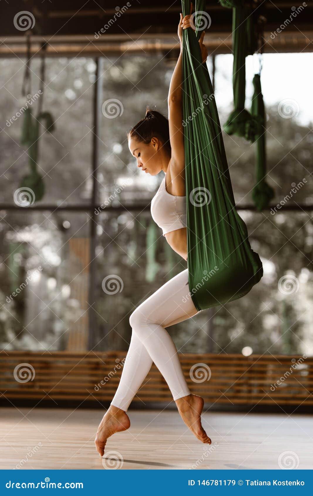 Молодая тонкая темн-с волосами девушка одетая в белых верхней части и колготках спорт делает протягивающ тренировку на зеленом га