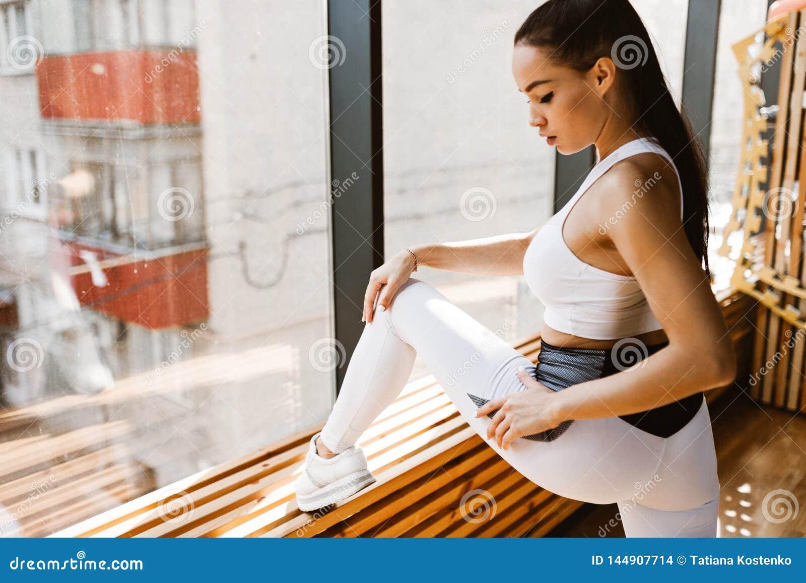 Молодая тонкая темн-с волосами девушка одетая в белых одеждах спорт де